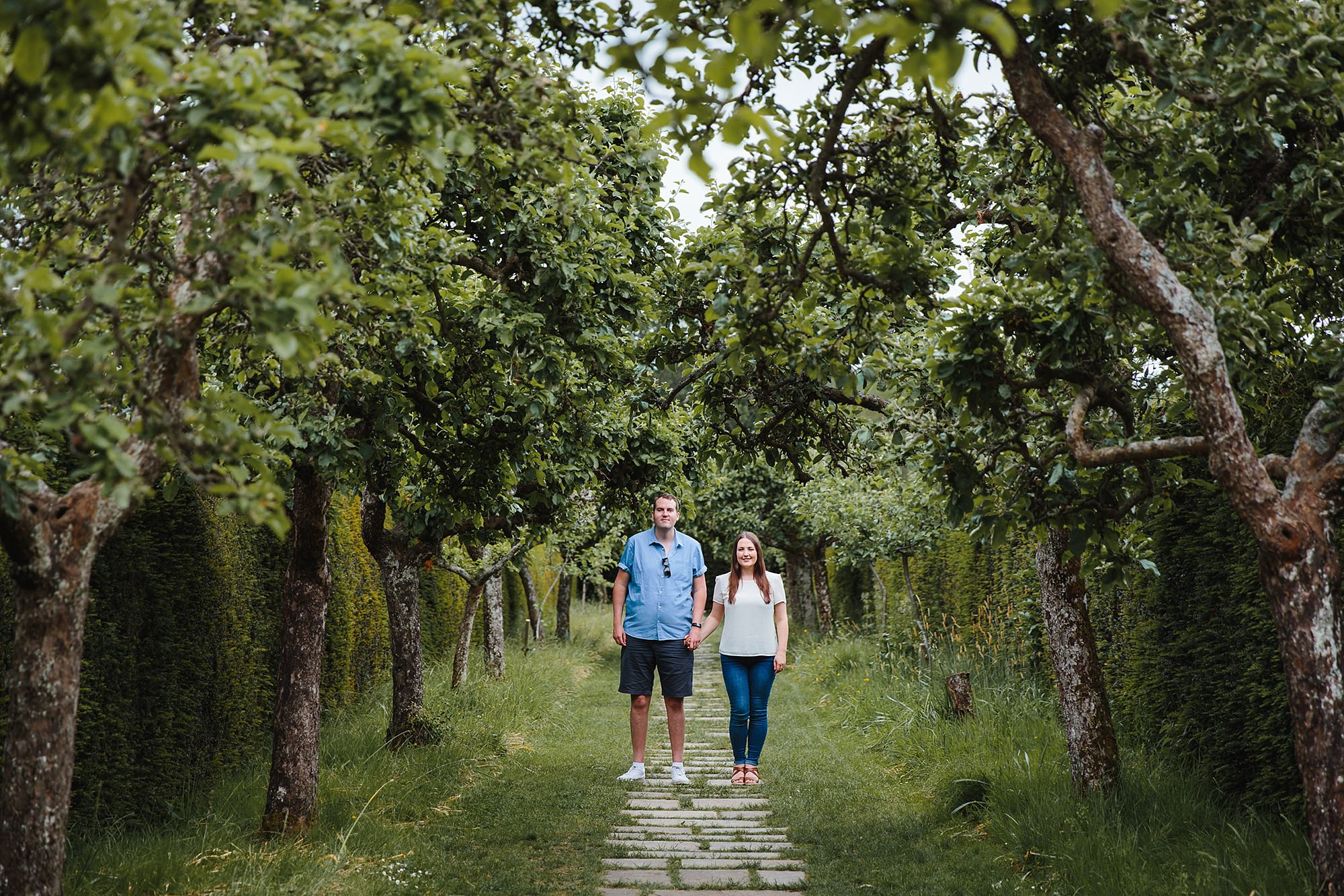 Tonbridge engagement photography couple stood in tree lined path