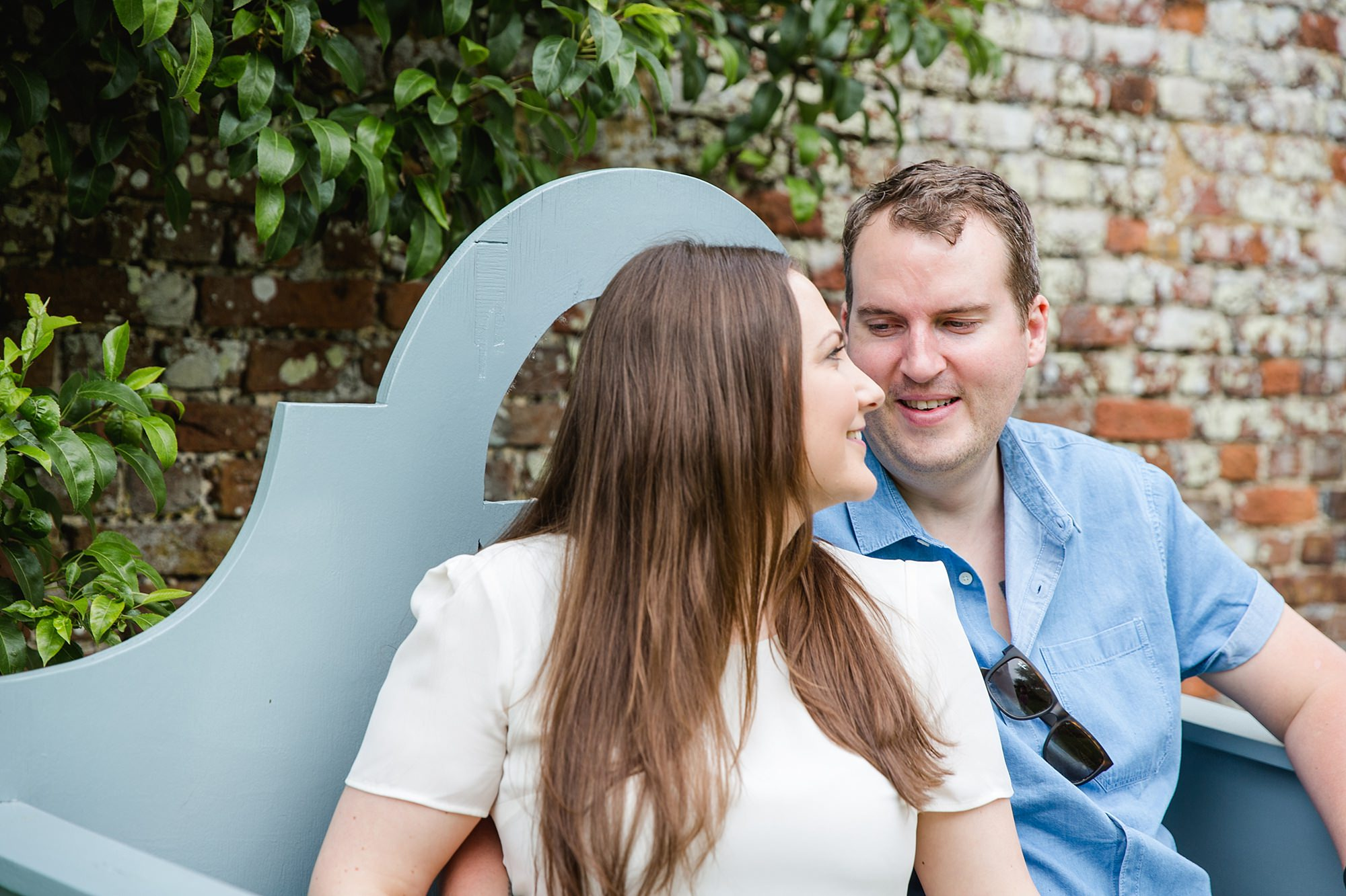 Tonbridge engagement photography a couple smile together on a bench