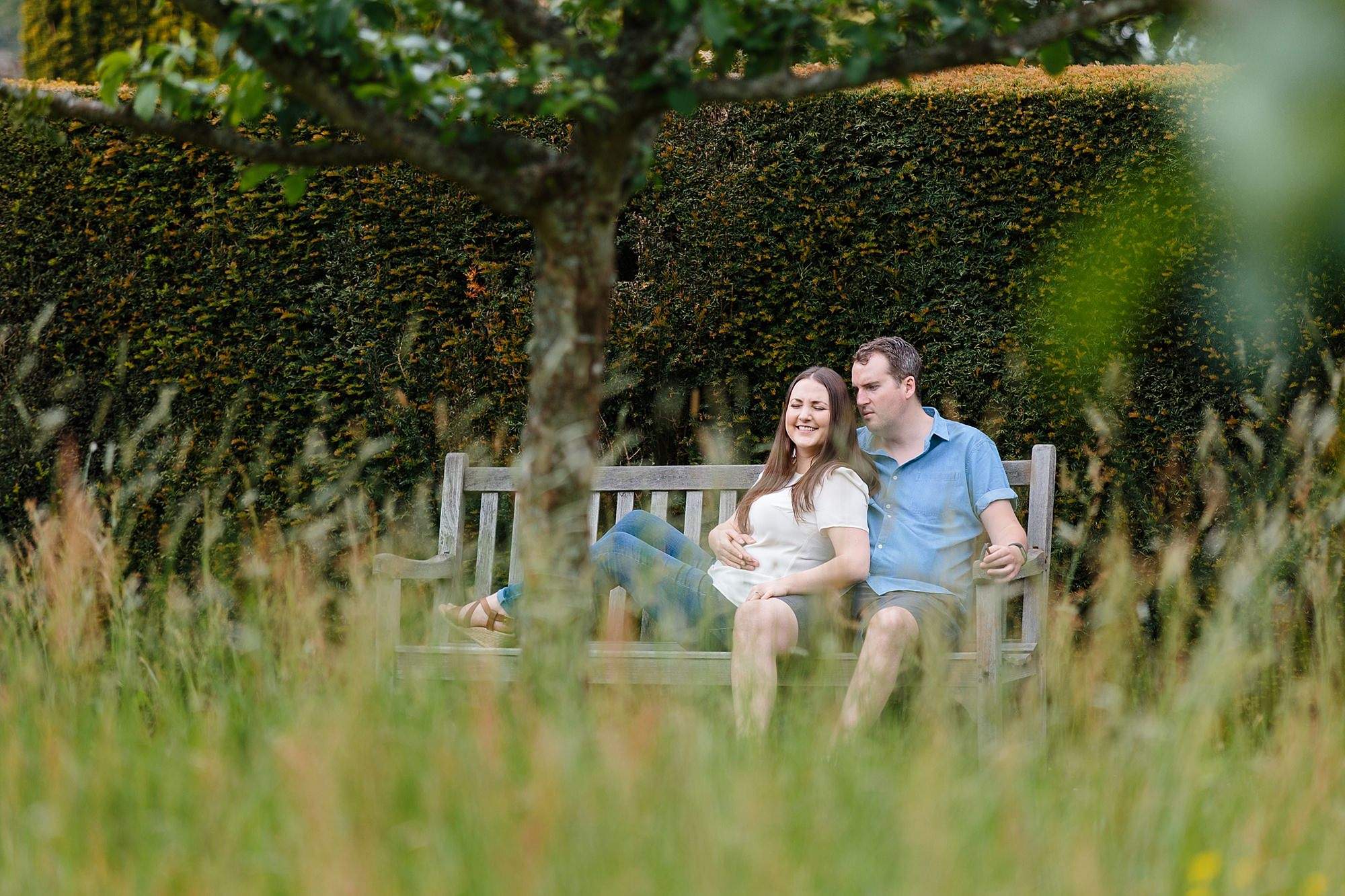 Tonbridge engagement photography - a couple laughs together on a bench