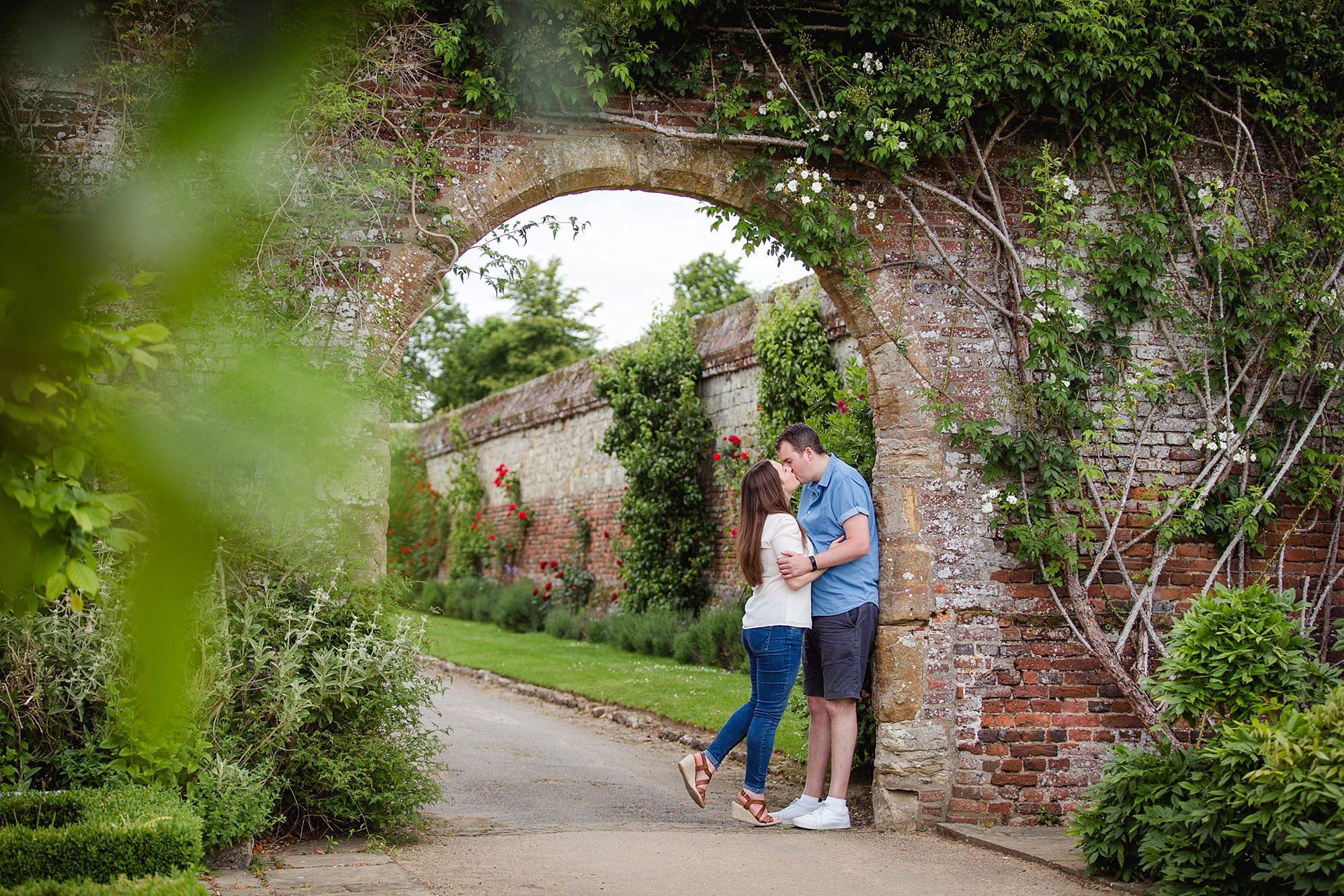 Tonbridge engagement photography portrait of a couple kissing under a bridge