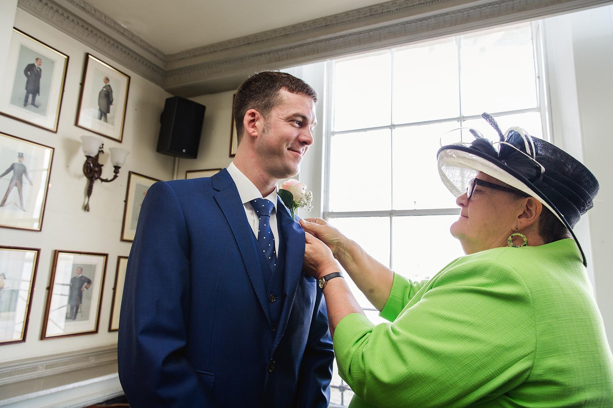 Trafalgar Tavern wedding groom's mum adjusts his buttonhole