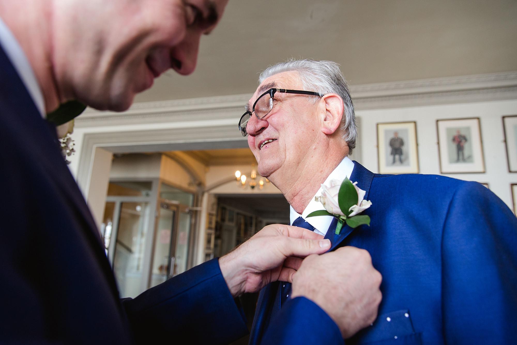 Trafalgar Tavern wedding groom puts on his father's buttonhole