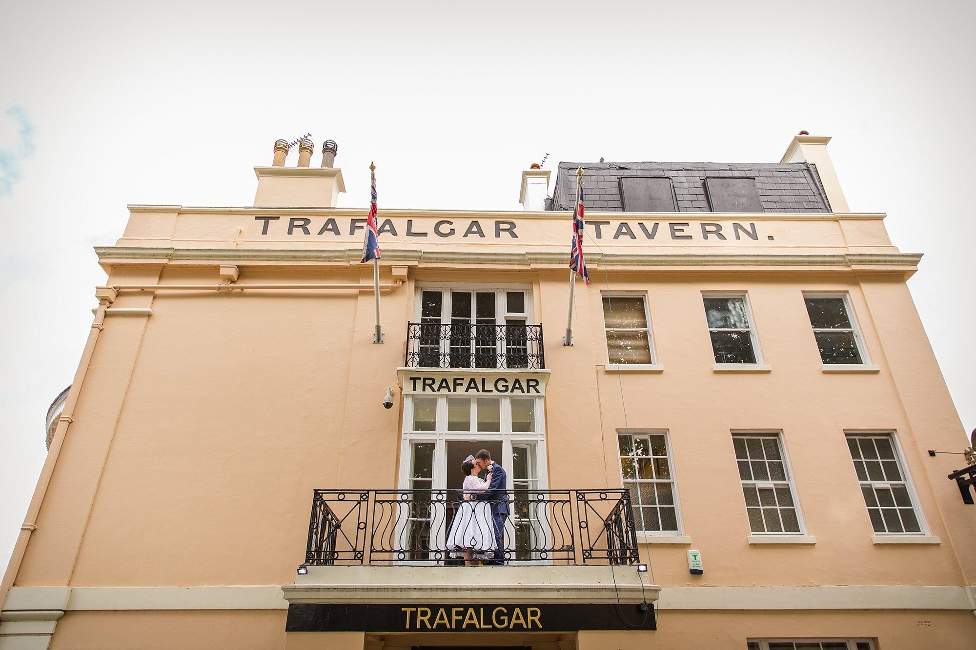 Trafalgar Tavern wedding bride and groom kiss on balcony