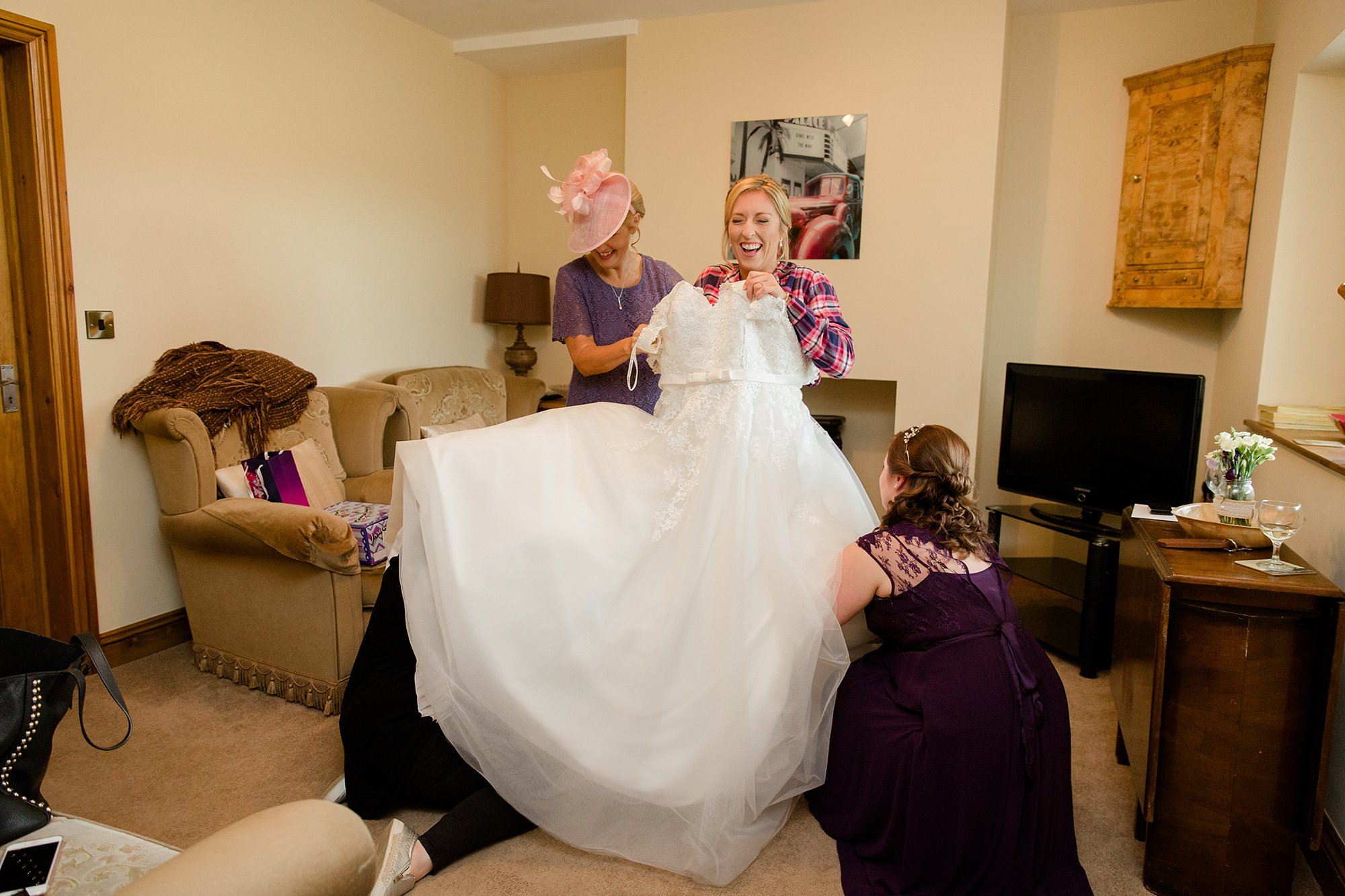 A fun wedding - bride laughing as she puts on dress