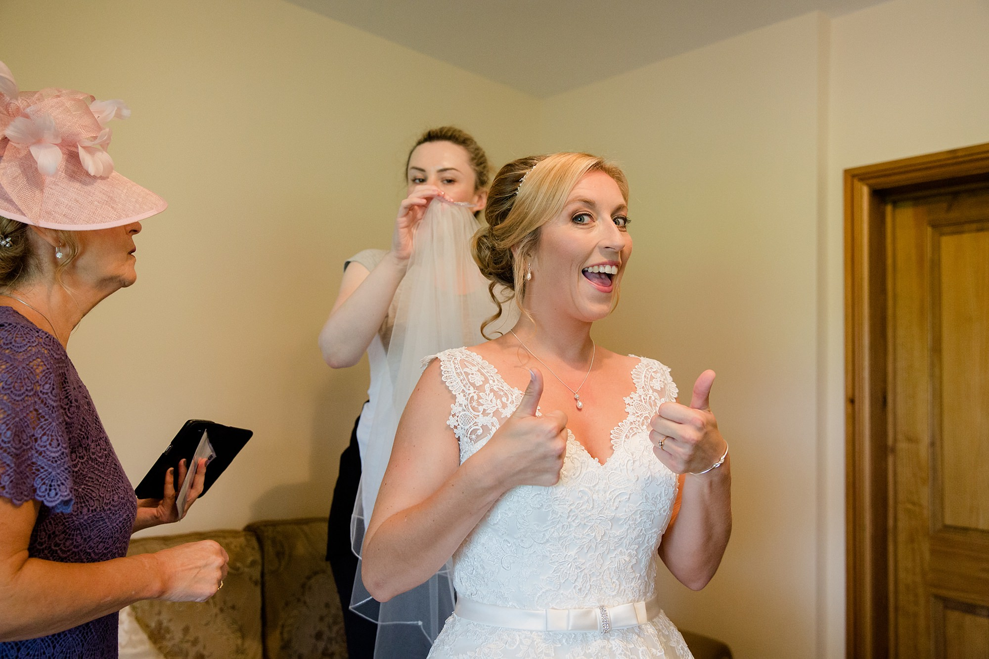 A fun wedding at Plas Isaf bride putting on her veil