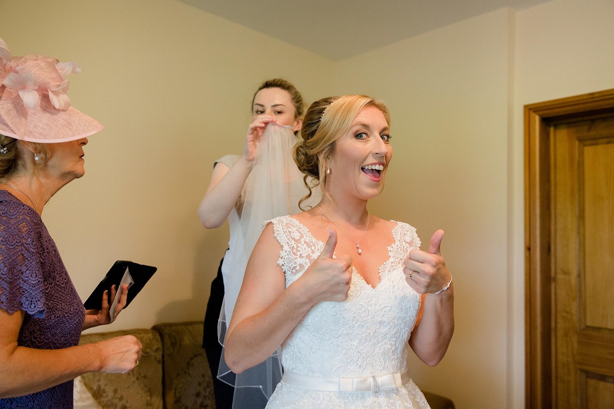 A fun wedding at Plas Isaf bride putting on her veil