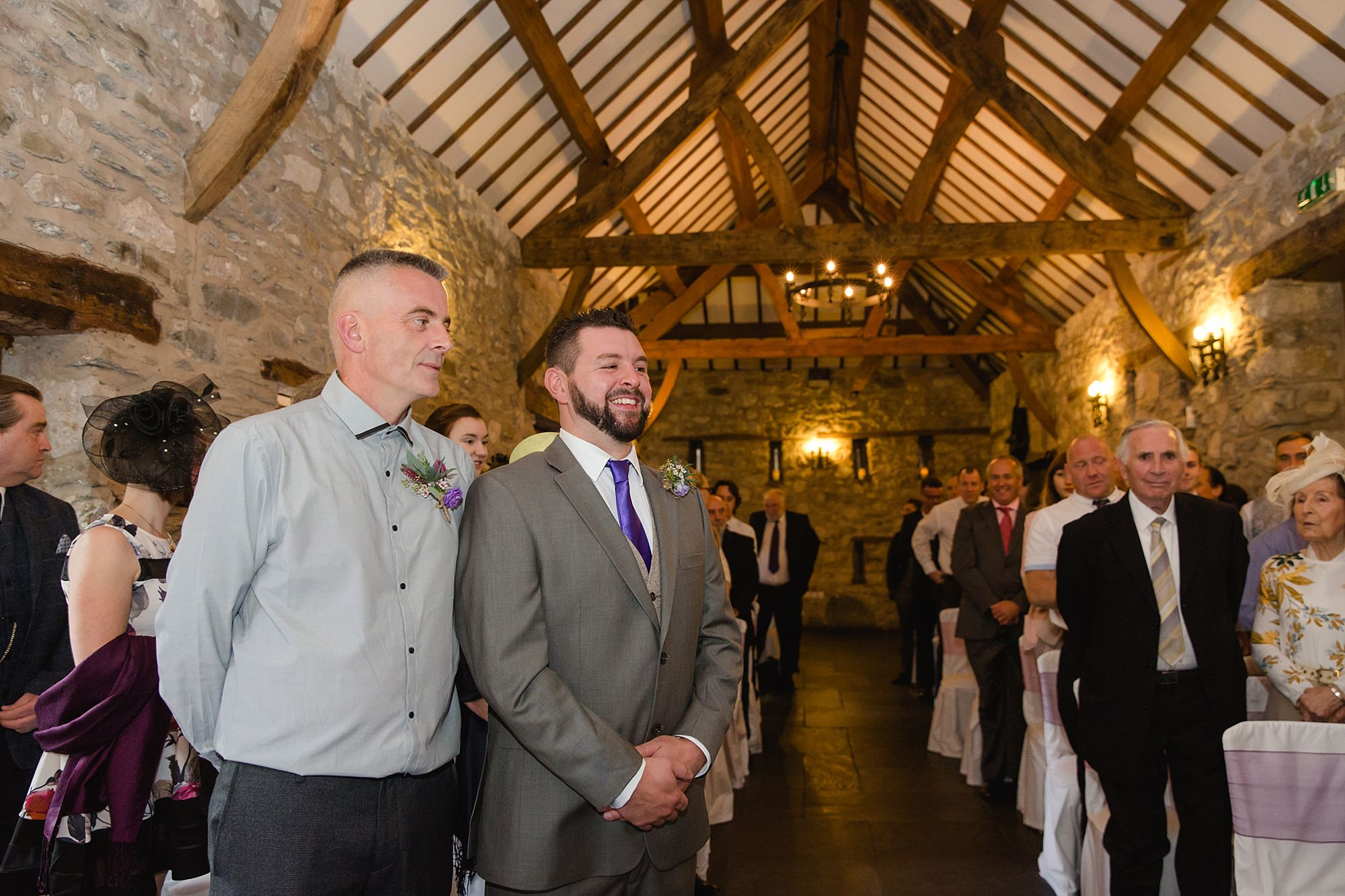 A fun wedding portrait of groom waiting for bride at Plas Isaf