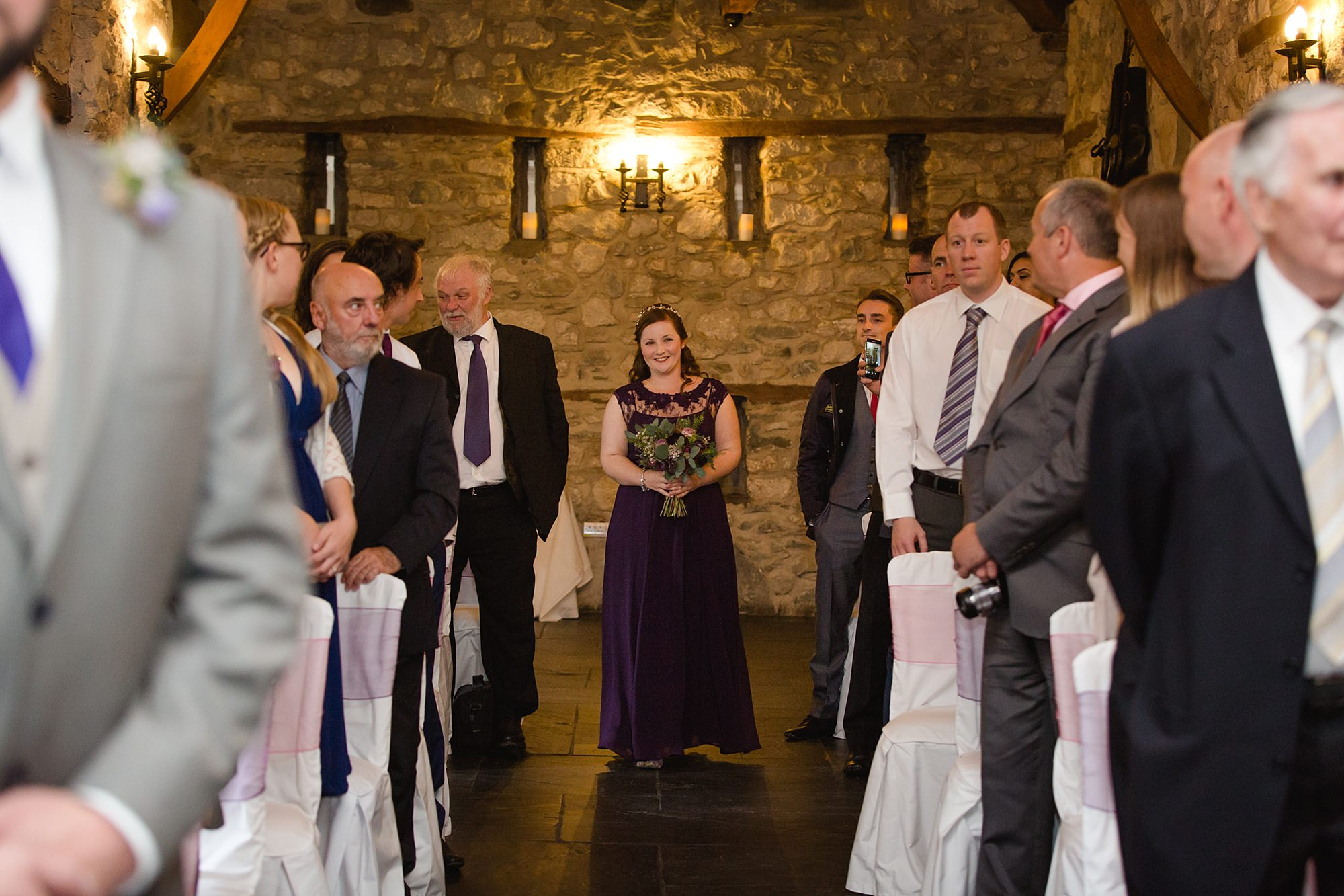 A fun wedding at Plas Isaf bridesmaid walking down aisle