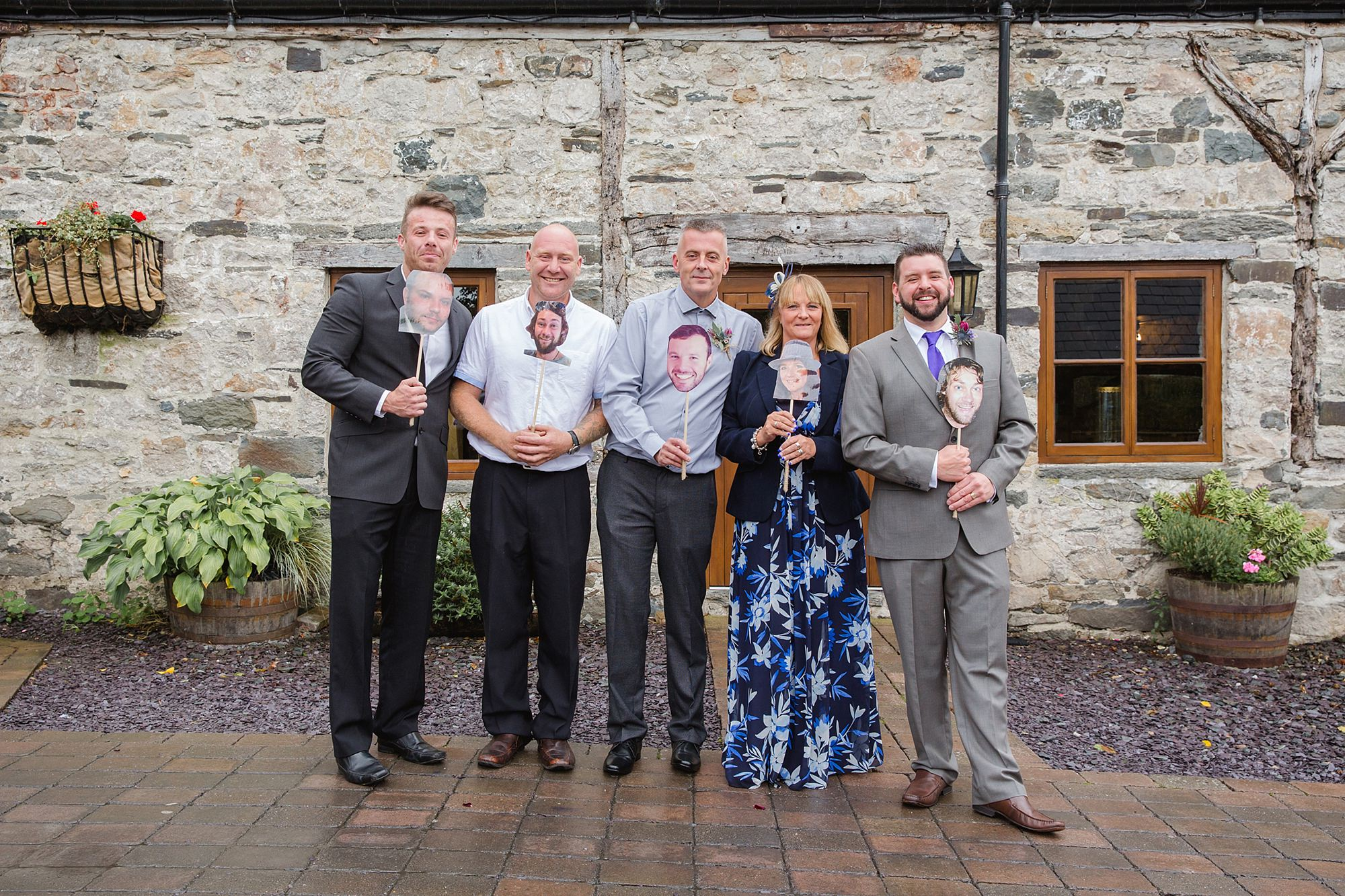 A fun wedding group photo with cutout heads