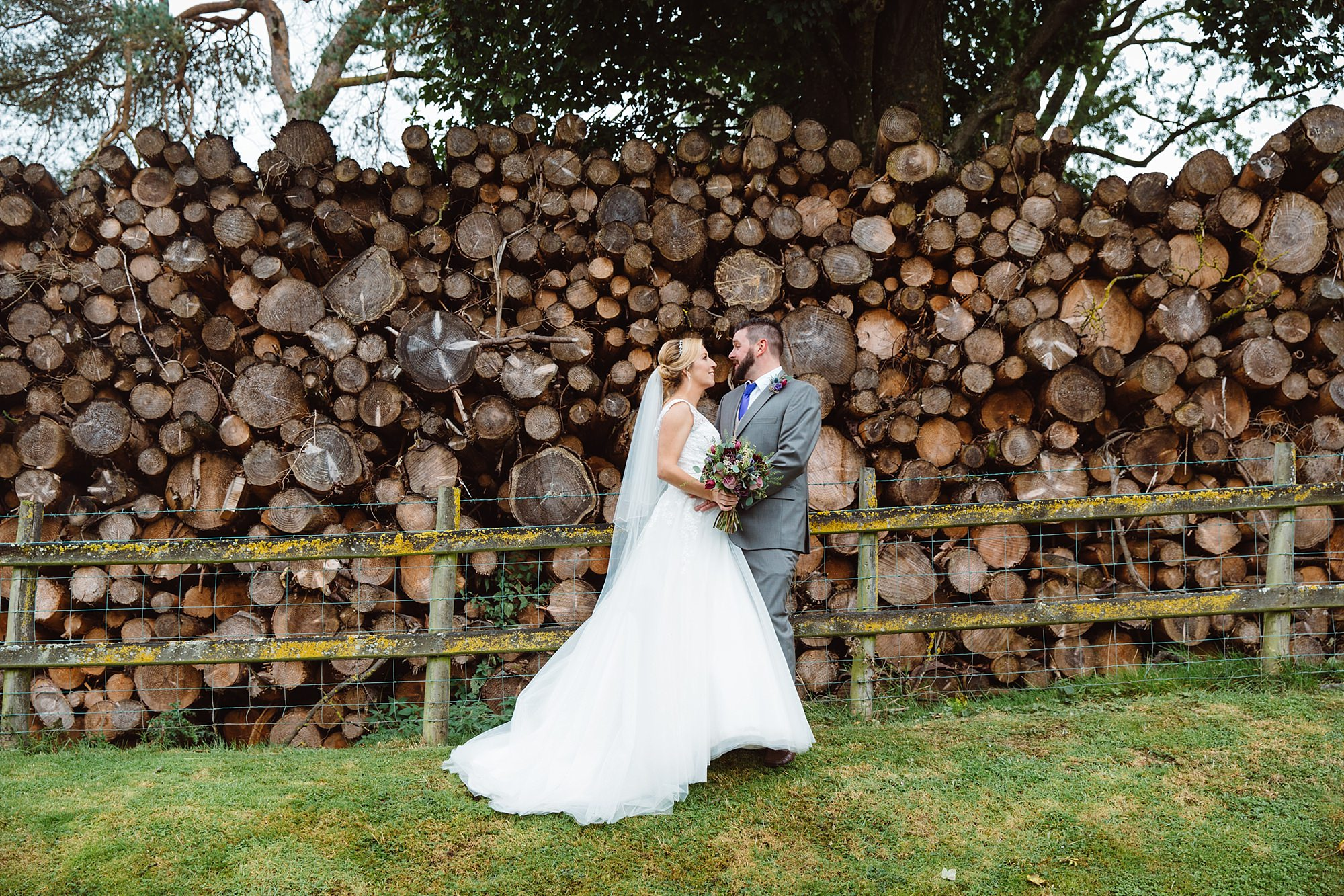 A fun wedding portrait of bride and groom in front of logs at Plas Isaf