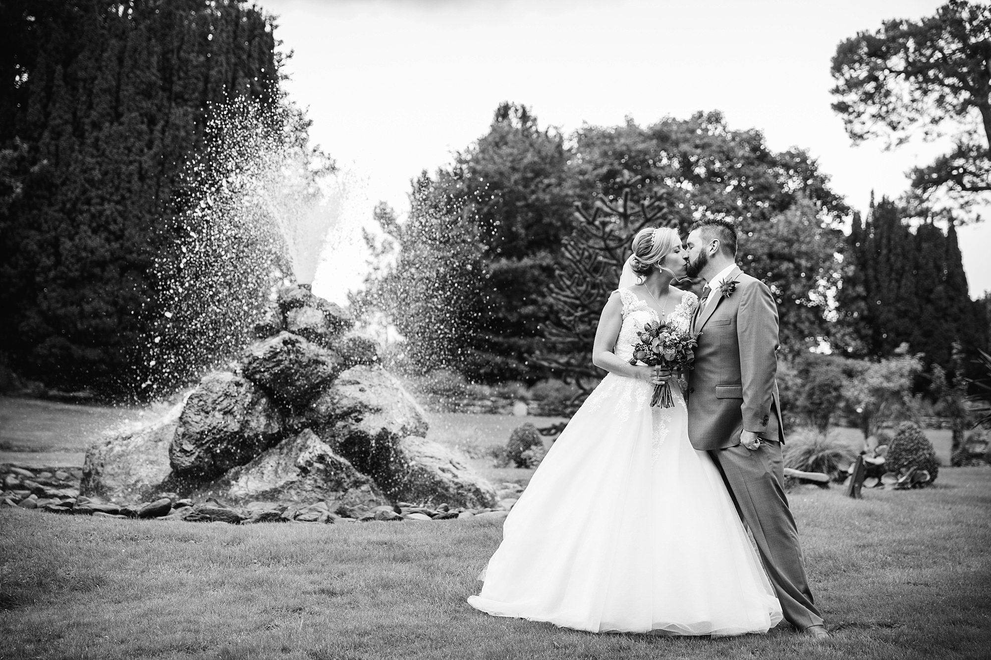 A fun wedding at Plas Isaf - bride and groom stand next to fountain