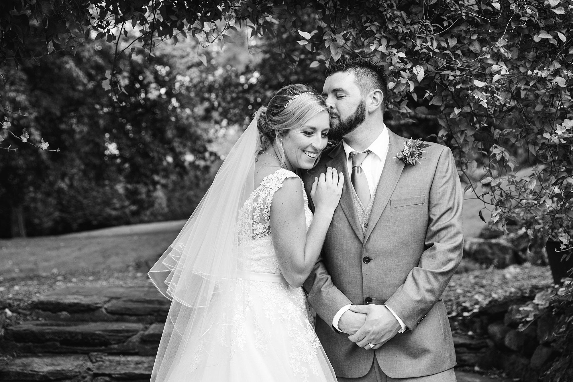 A fun wedding at Plas Isaf - portrait of groom kissing bride