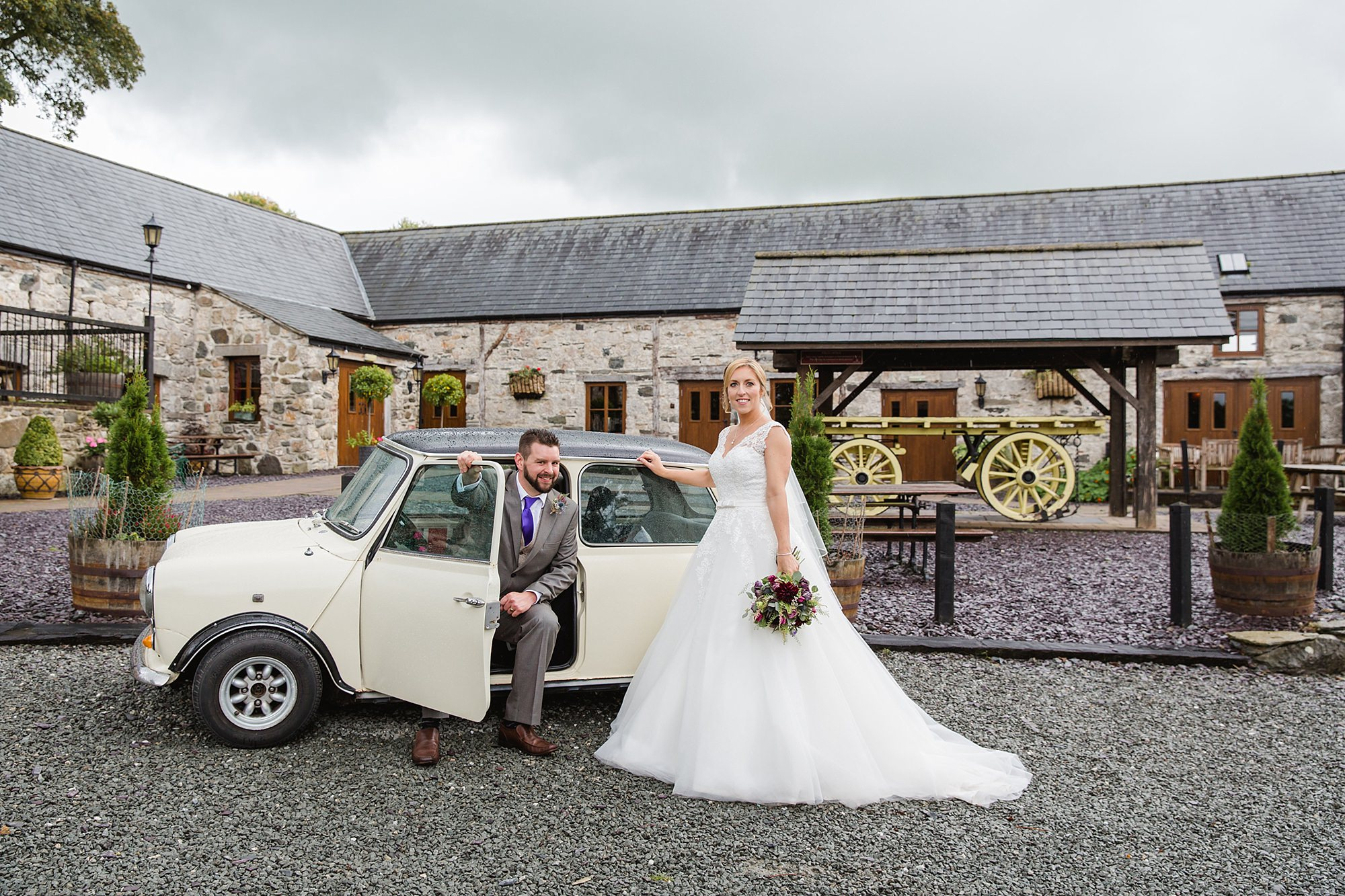 A fun wedding portrait of bride and groom with classic Mini Cooper