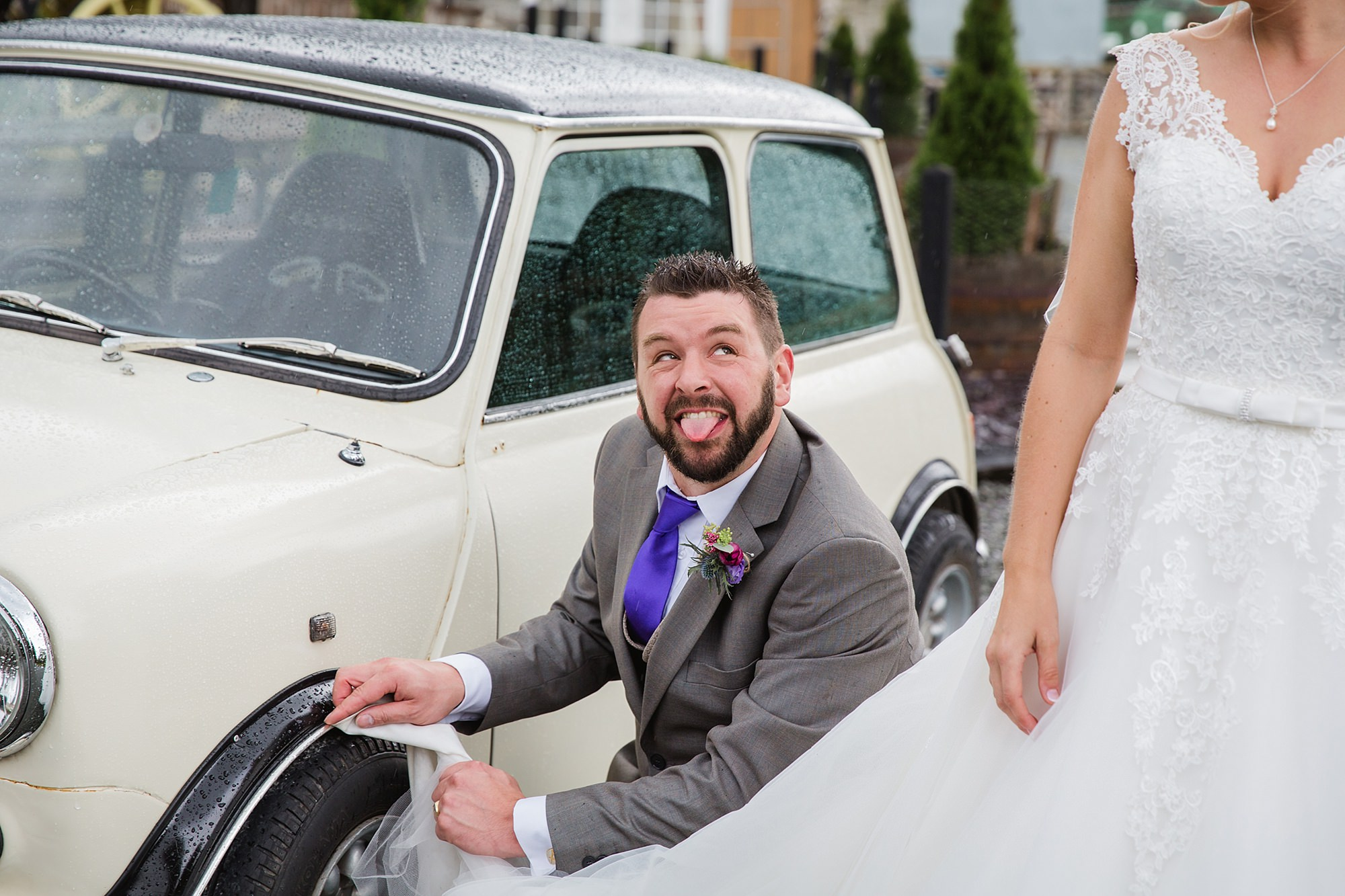 A fun wedding portrait of groom pretending to clean his car with bride's wedding dress
