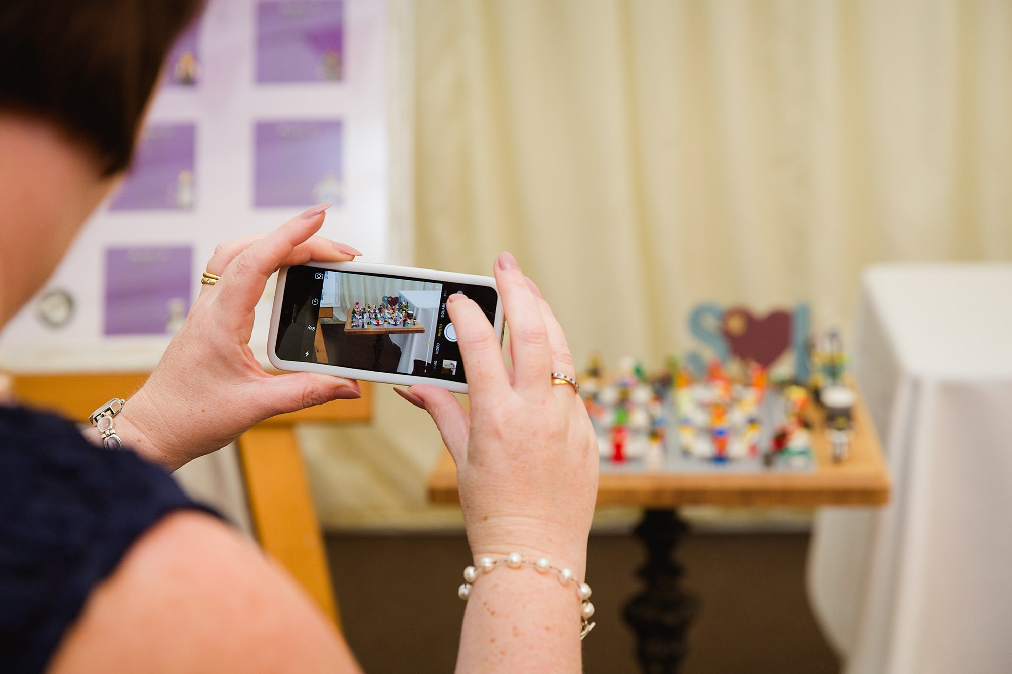 A fun wedding guest taking picture of lego table plan at Plas Isaf wedding