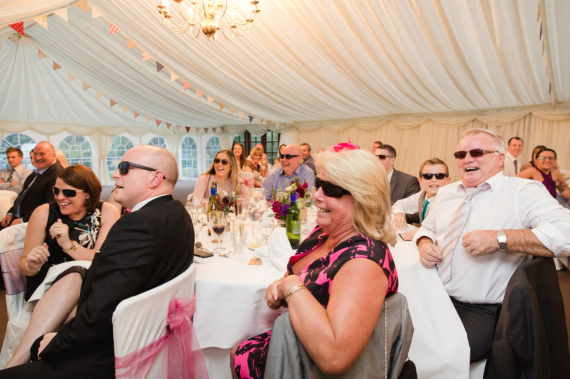 A fun wedding portrait of guests wearing sunglasses during speeches