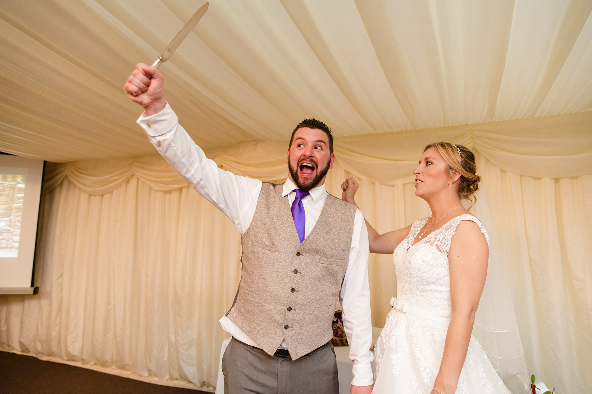 A fun wedding portrait of groom with knife before gutting cake