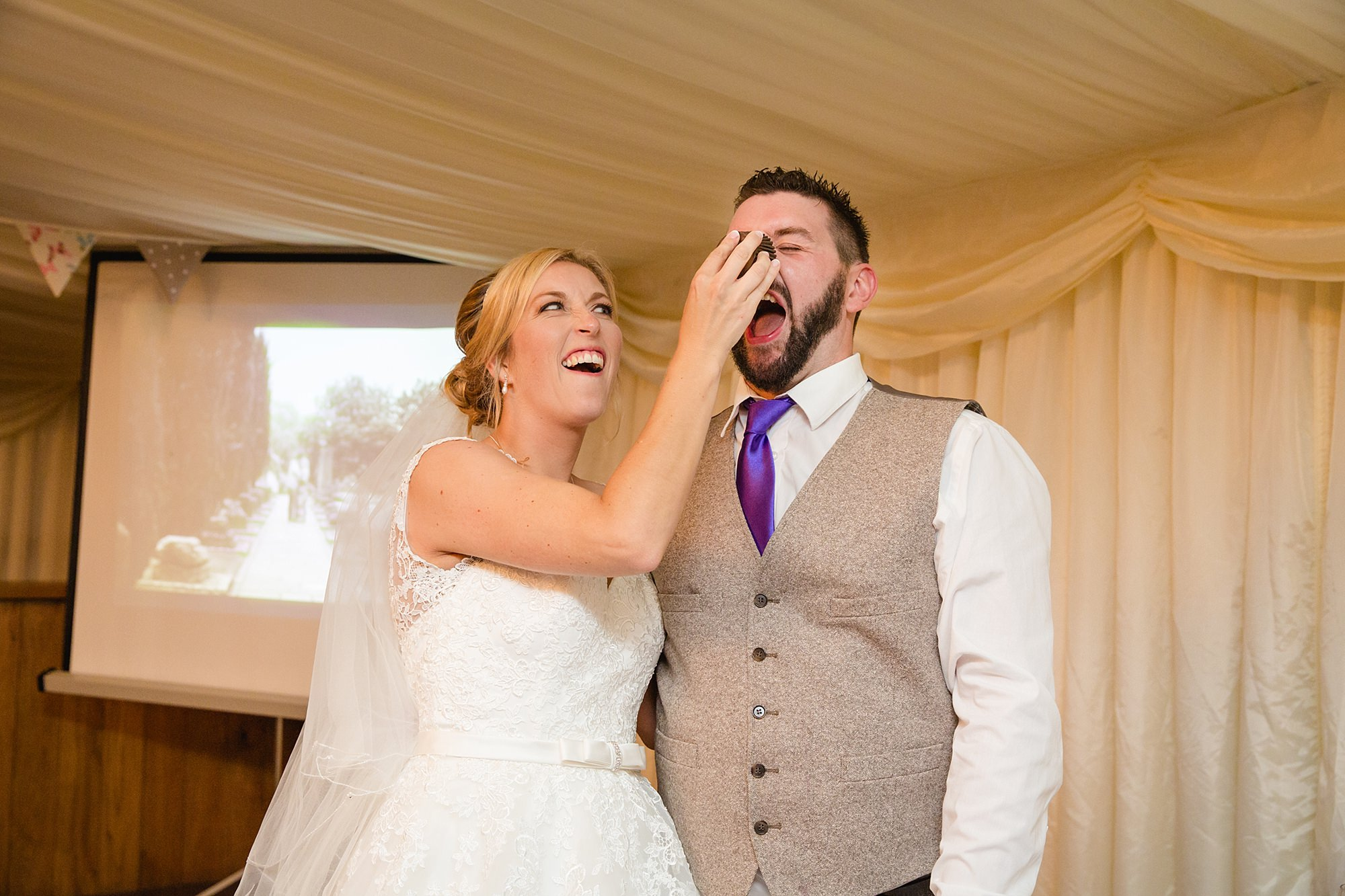 A fun wedding portrait of bride smashing cake in the groom's face