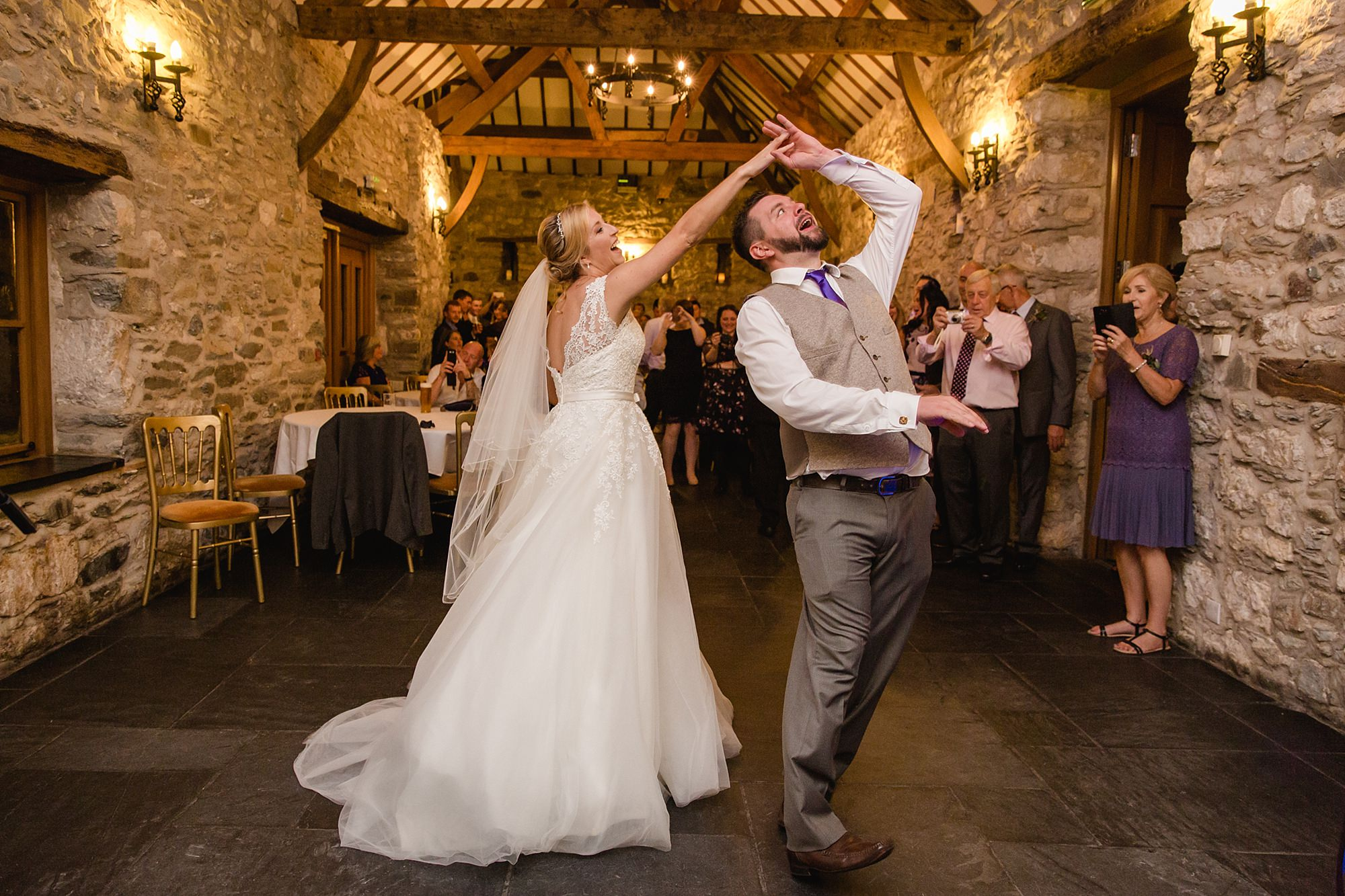 A fun wedding picture of bride attempting to twirl groom