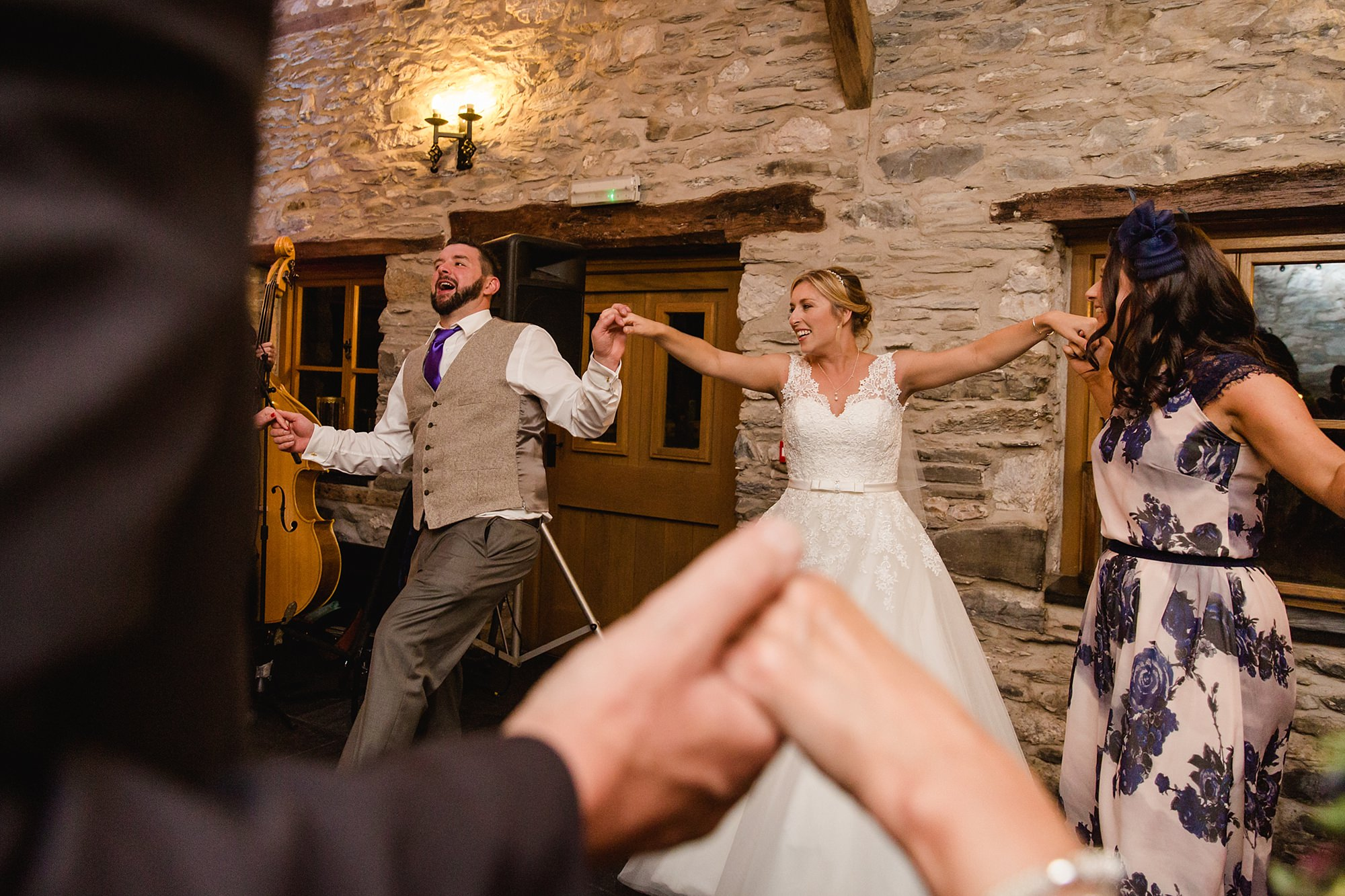A fun wedding picture of guests dancing at Plas Isaf