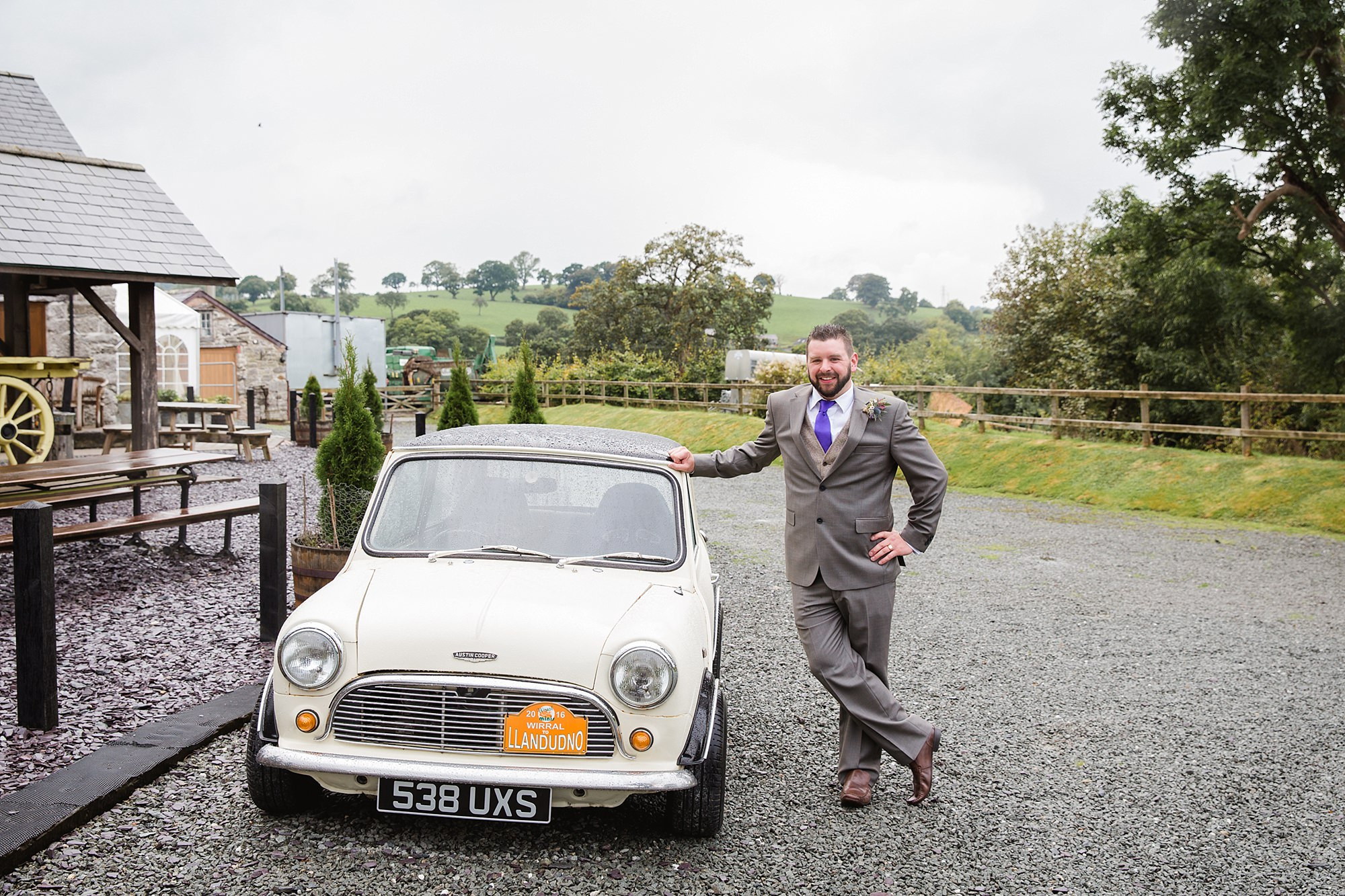 A fun wedding portrait of groom with his mini cooper