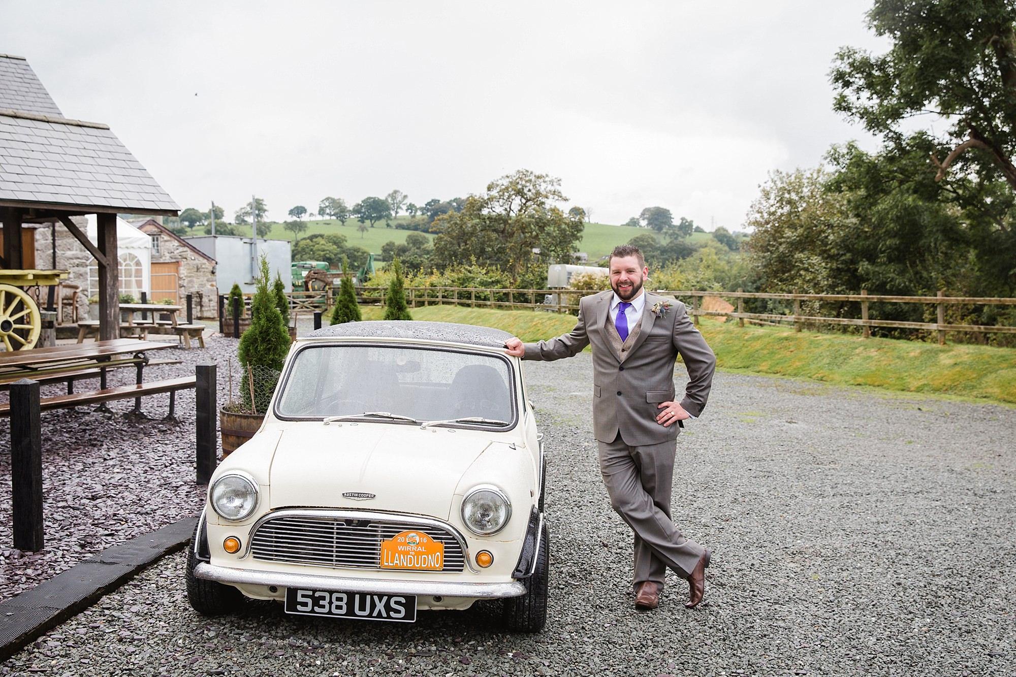 A fun wedding portrait of groom with his mini cooper
