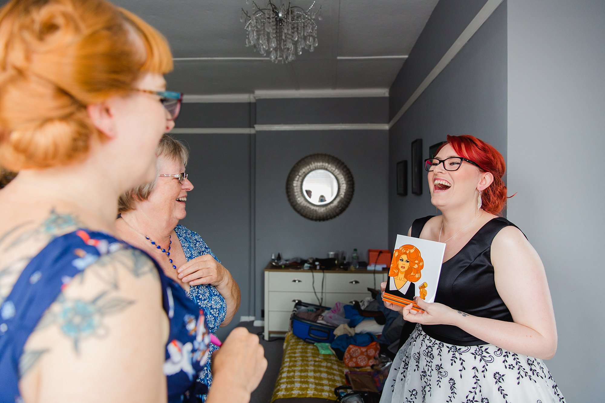 Beacon House wedding bride laughs with gift from bridesmaid