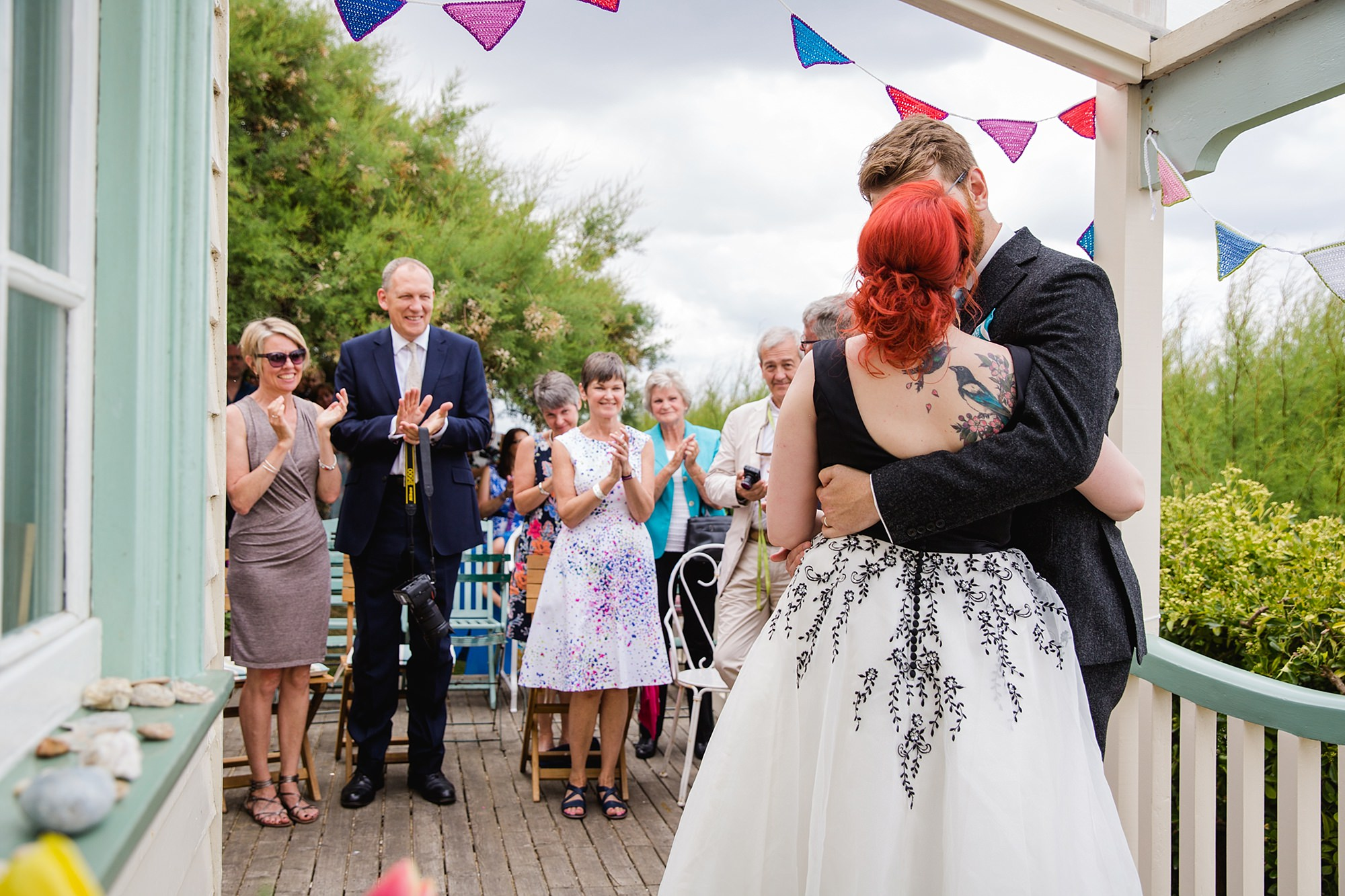 Beacon House wedding bride and groom kiss as guests clap