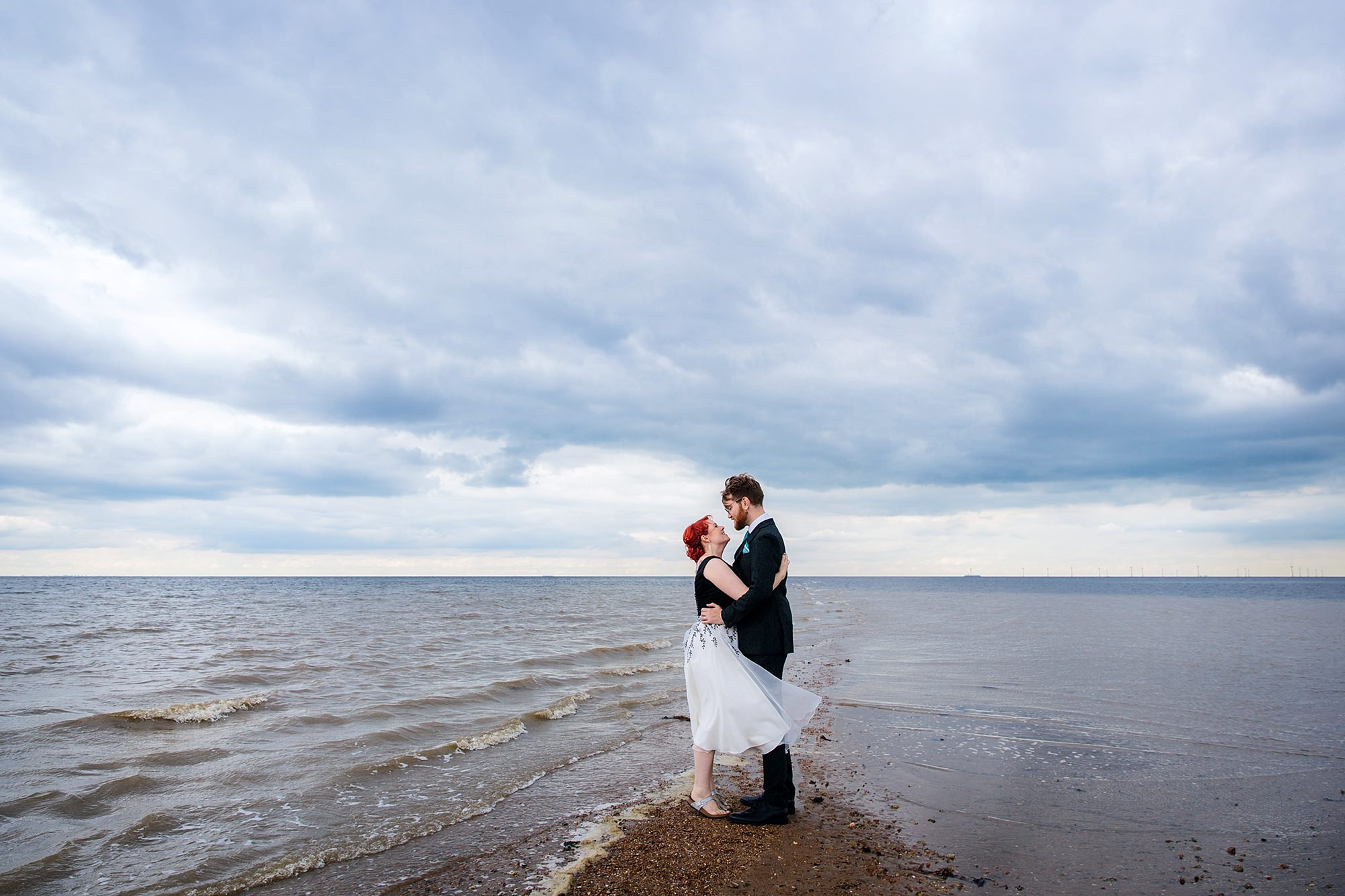 Beacon House wedding a bride and groom stand on the beach at whitstable