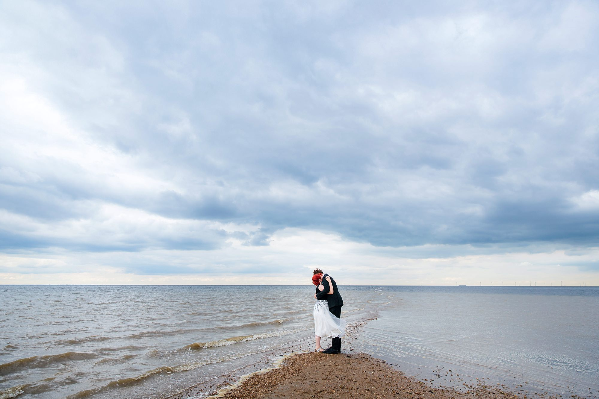 a bride and room on the end of a spit on the beach in whitstable