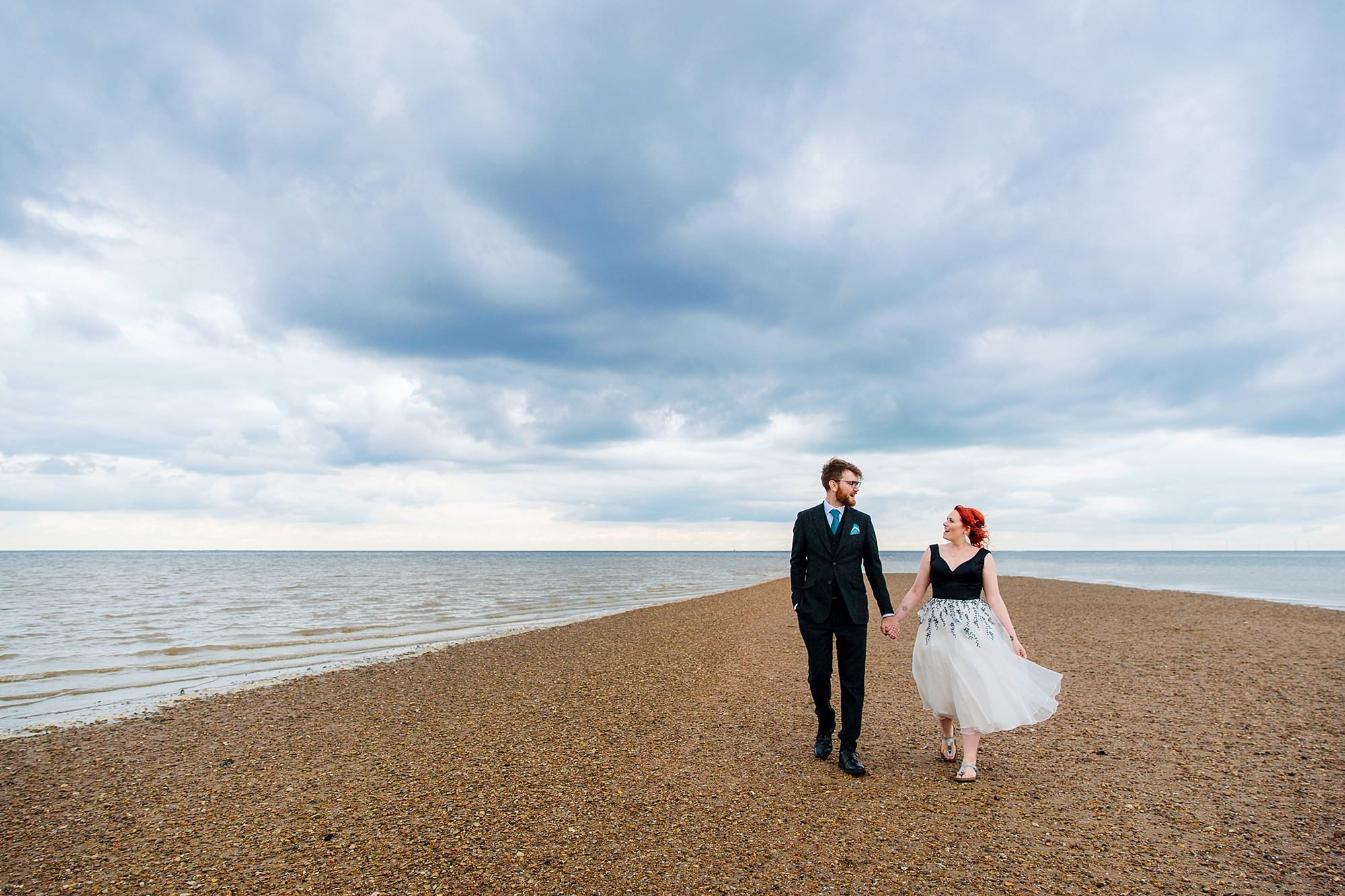 portrait of bride and groom walking along whitstable beach