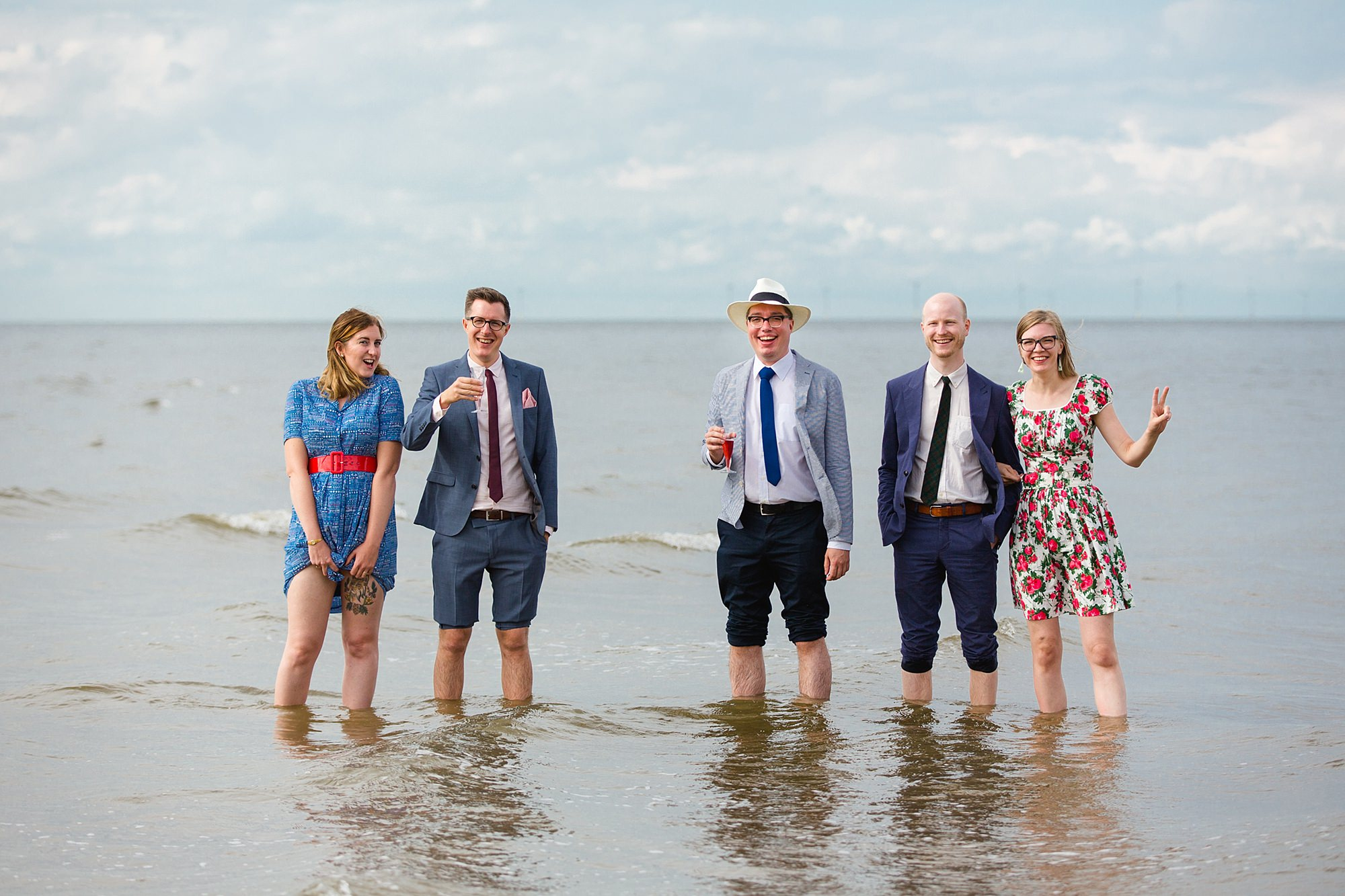 Beacon House wedding guests pose in the sea for a picture