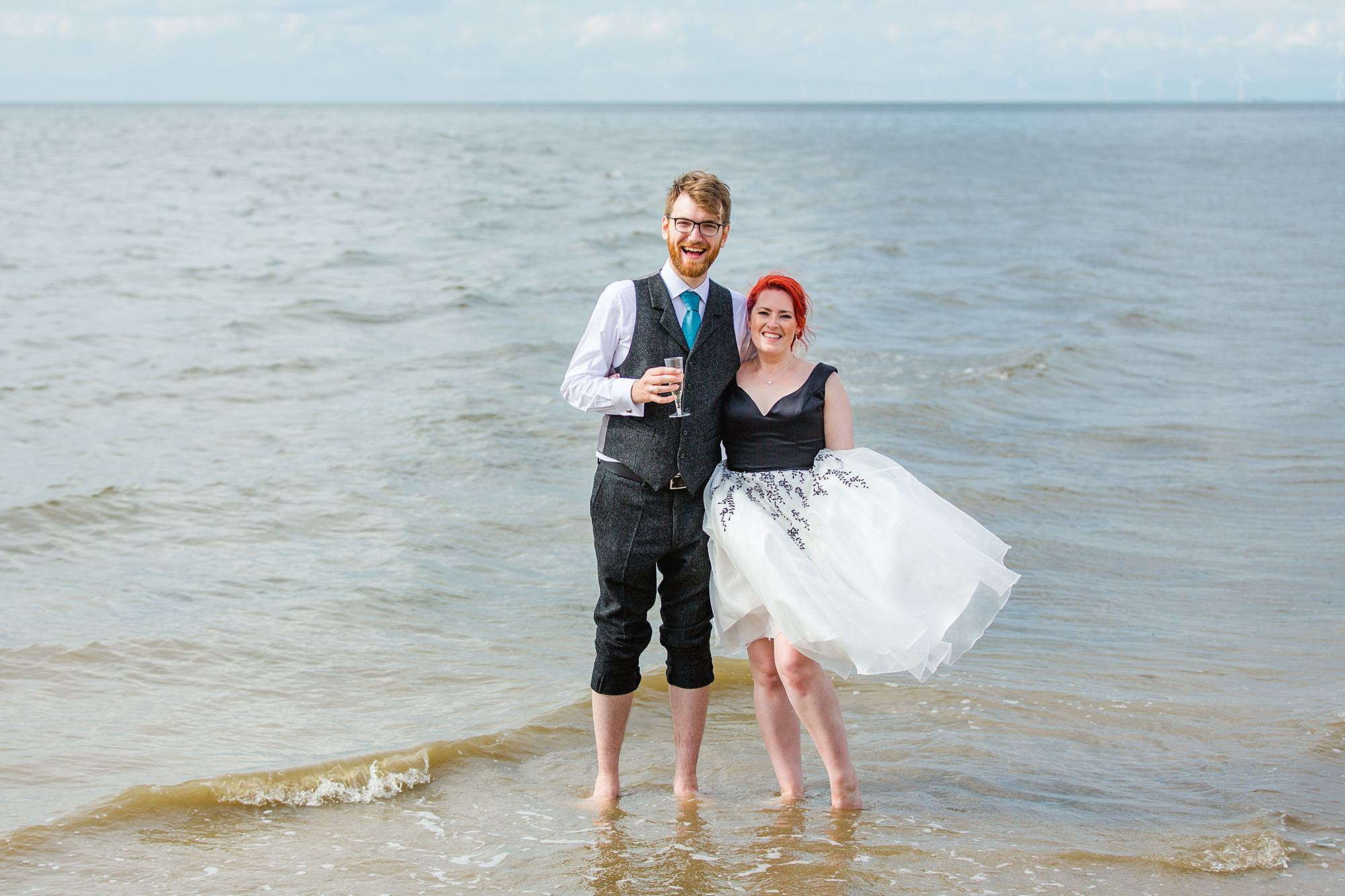 Beacon House wedding bride and groom paddle pose in the sea