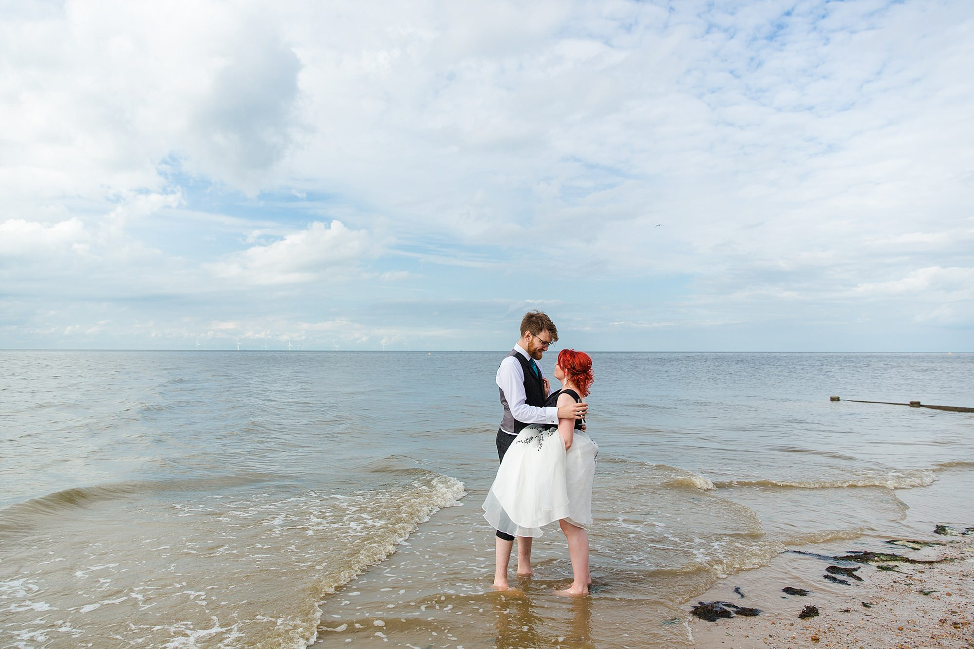 Beacon House wedding bride and groom paddling in the sea at whitstable