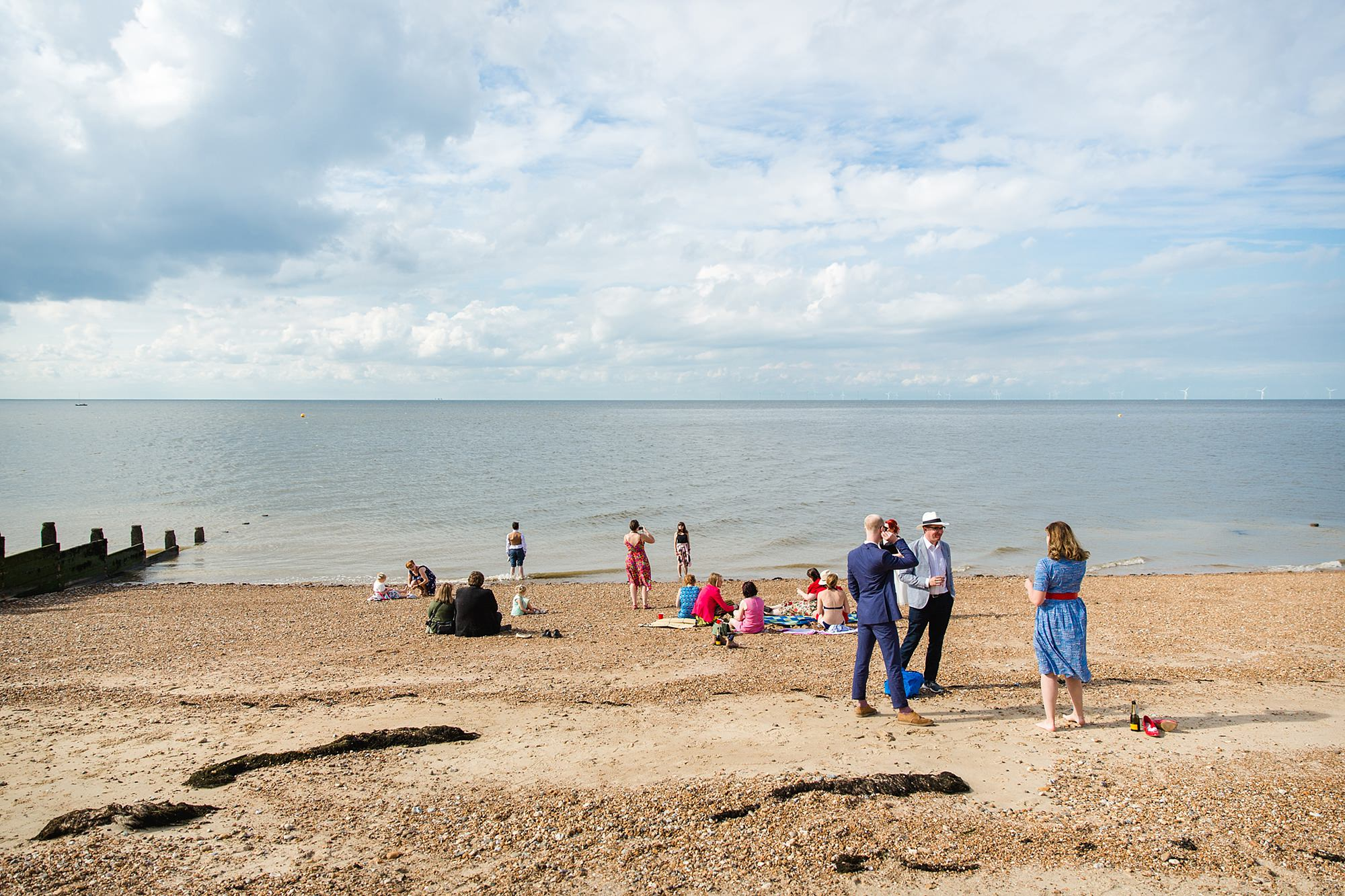 Beacon House wedding guests stood on the beach in whitstable