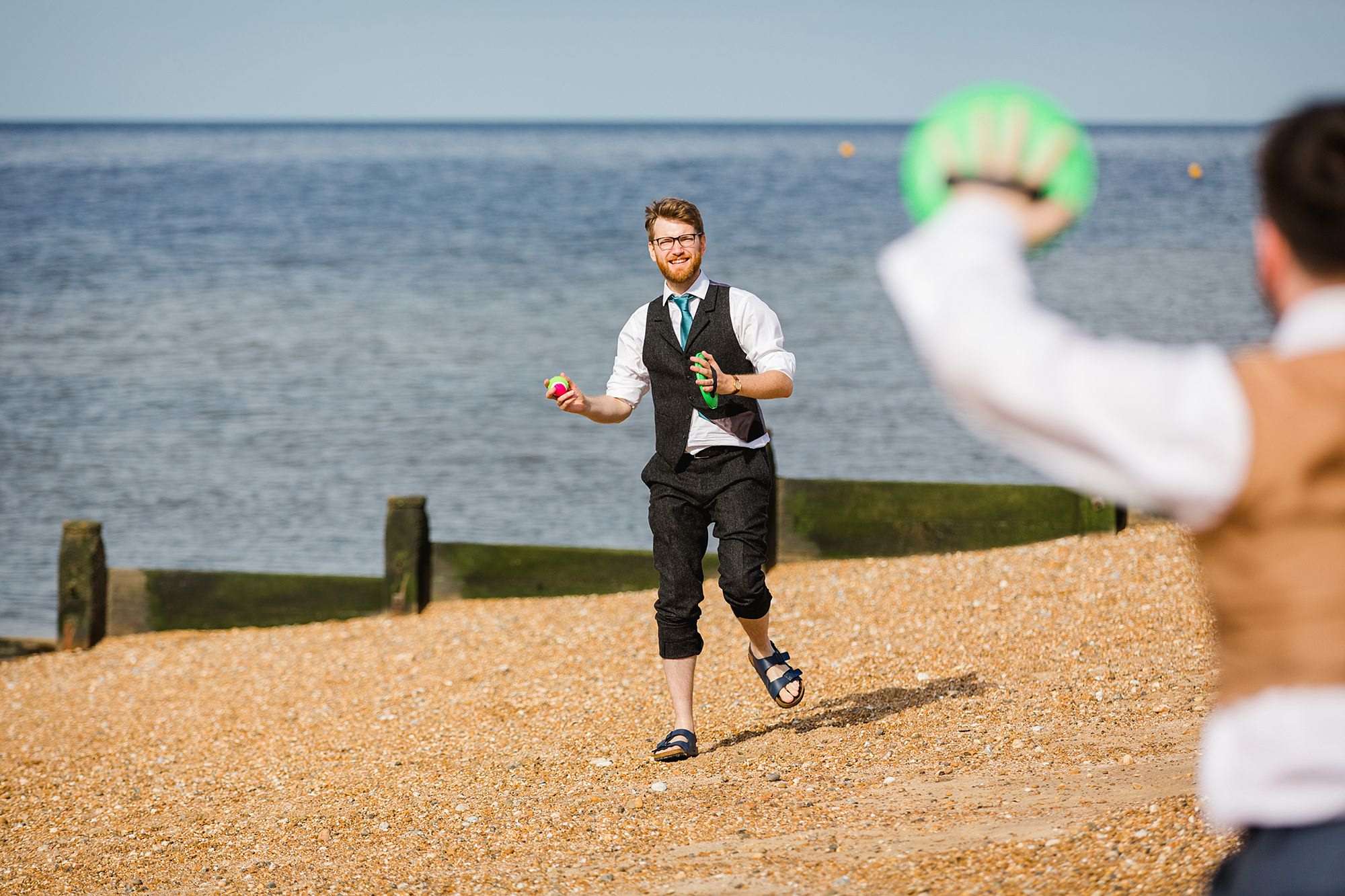Beacon House wedding groom playing catch on whitstable beach