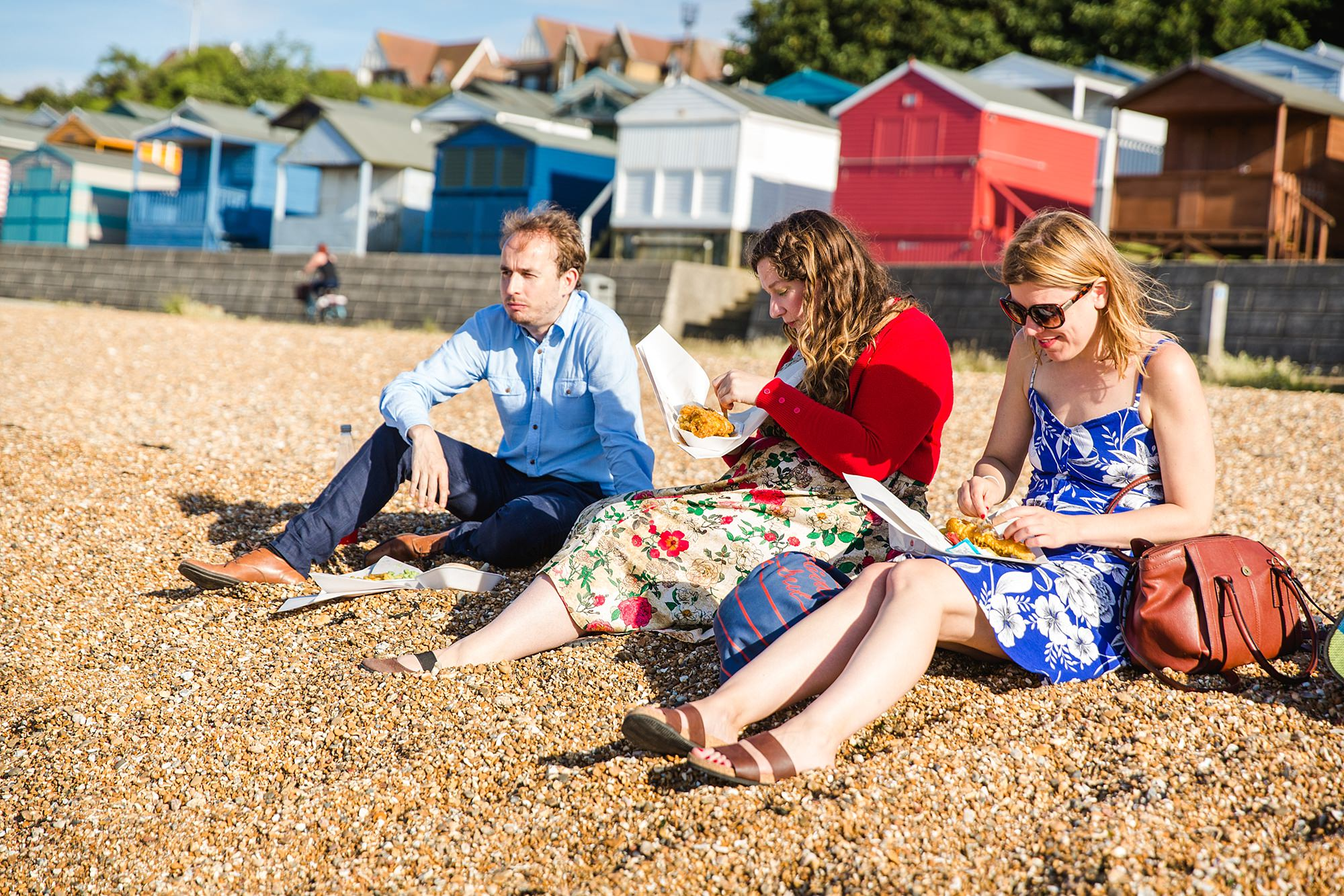 Beacon House wedding guests eat fish and chips on the beach