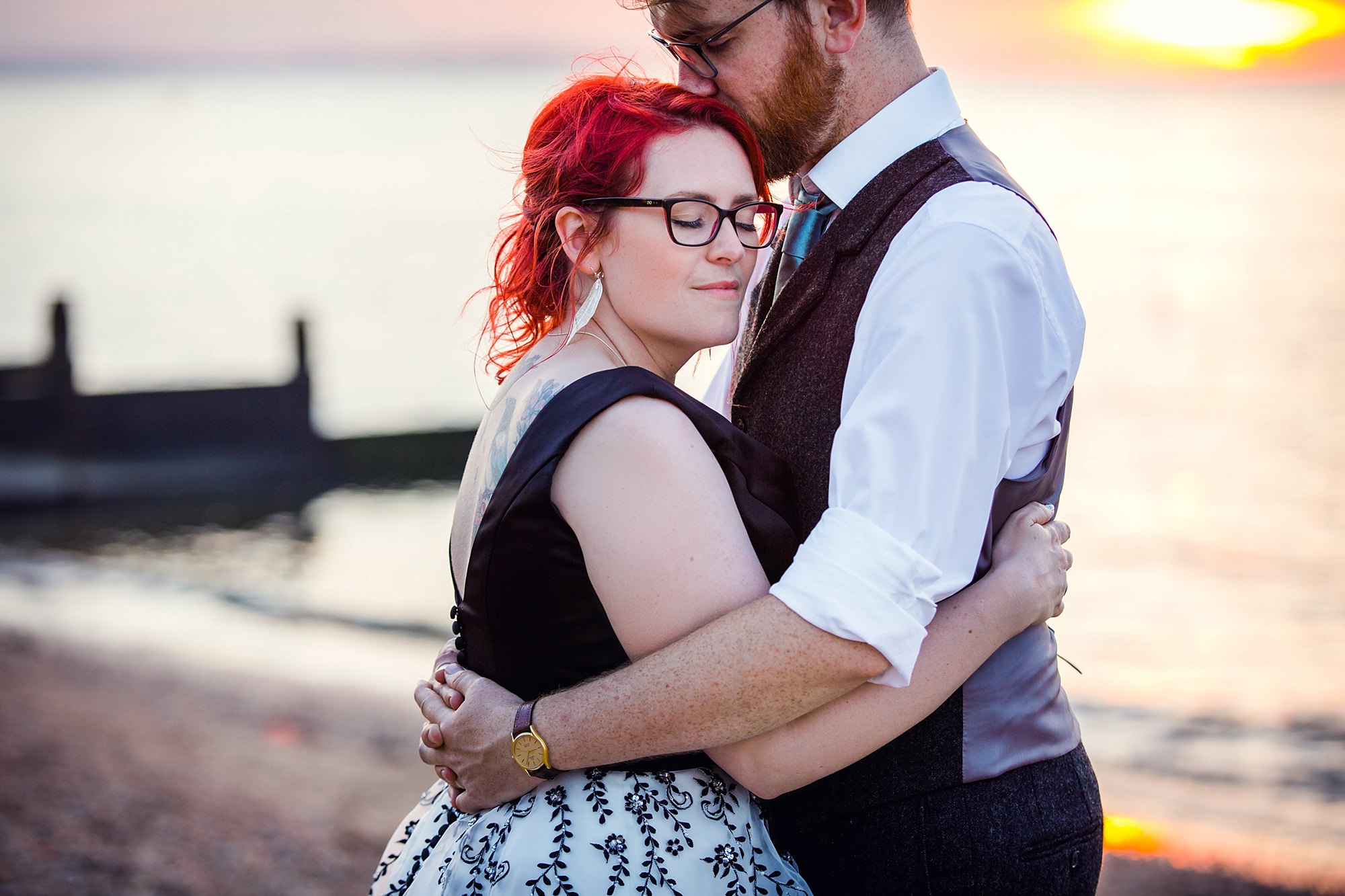 Beacon House wedding bride hugs groom during sunset portrait on the beach