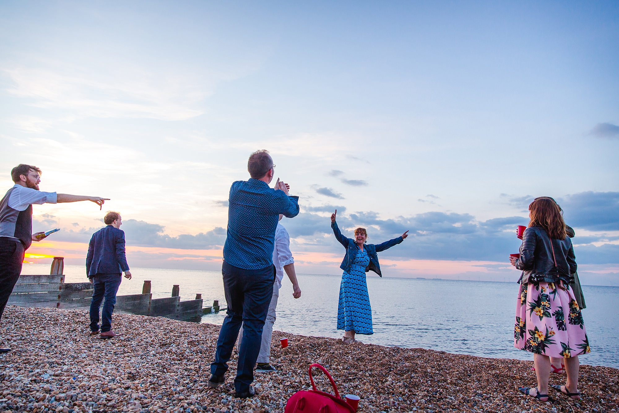 Beacon House wedding guest cheers isn she throws stone into the sea on whitstable beach