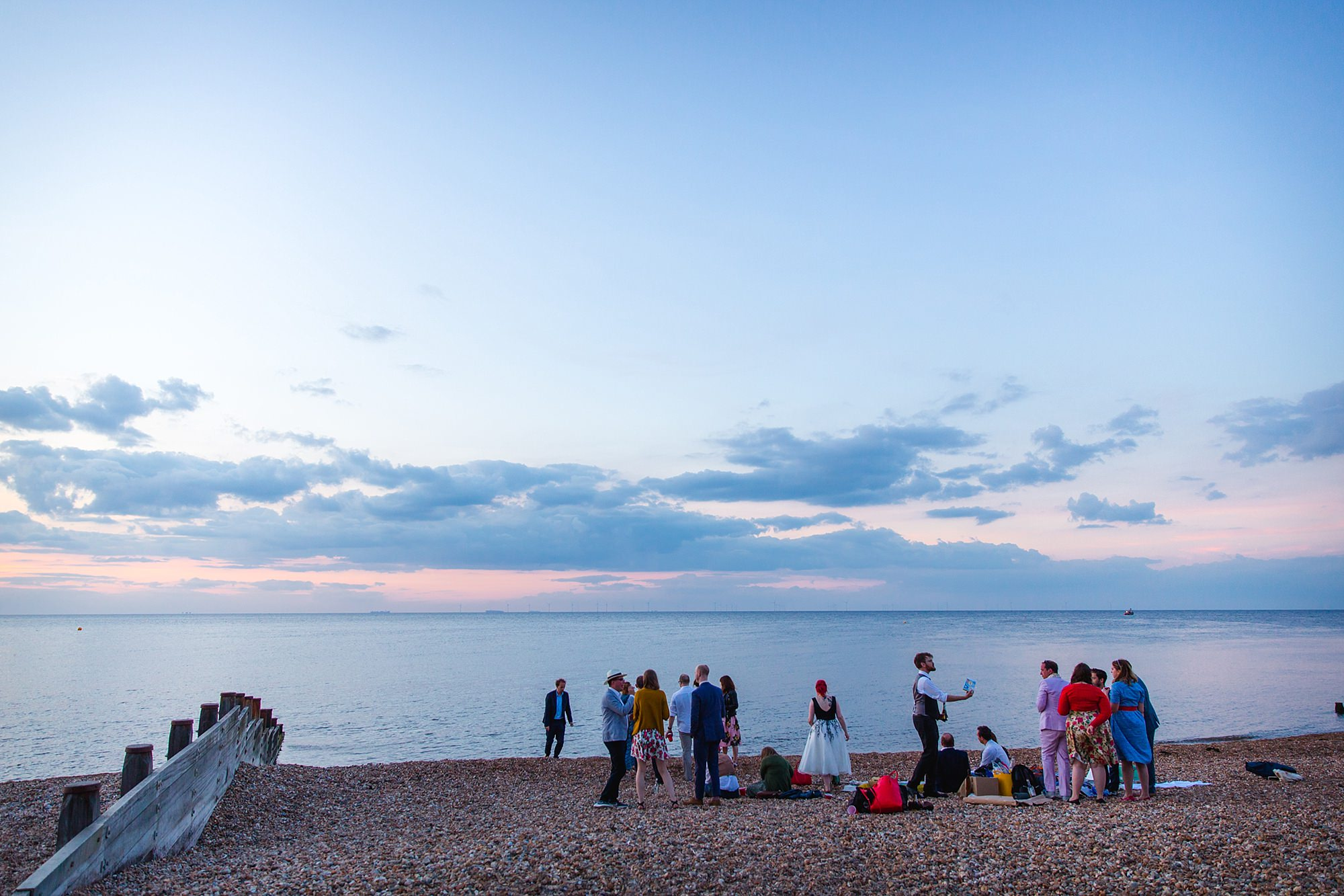 Beacon House wedding guests enjoying sunset together on whitstable beach