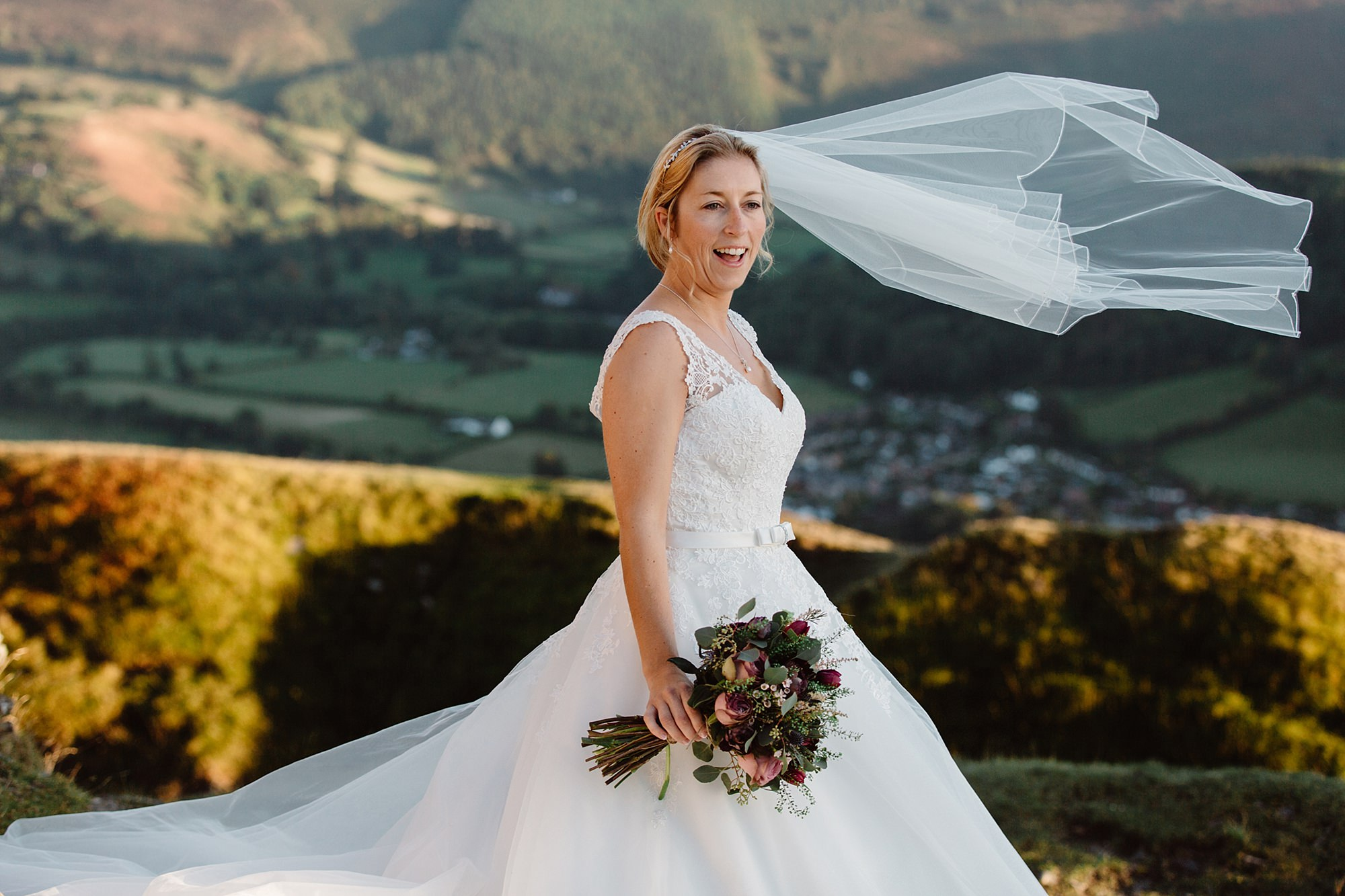 Castell dinas bran wedding photography a bride laughs as her veil blows in the wind