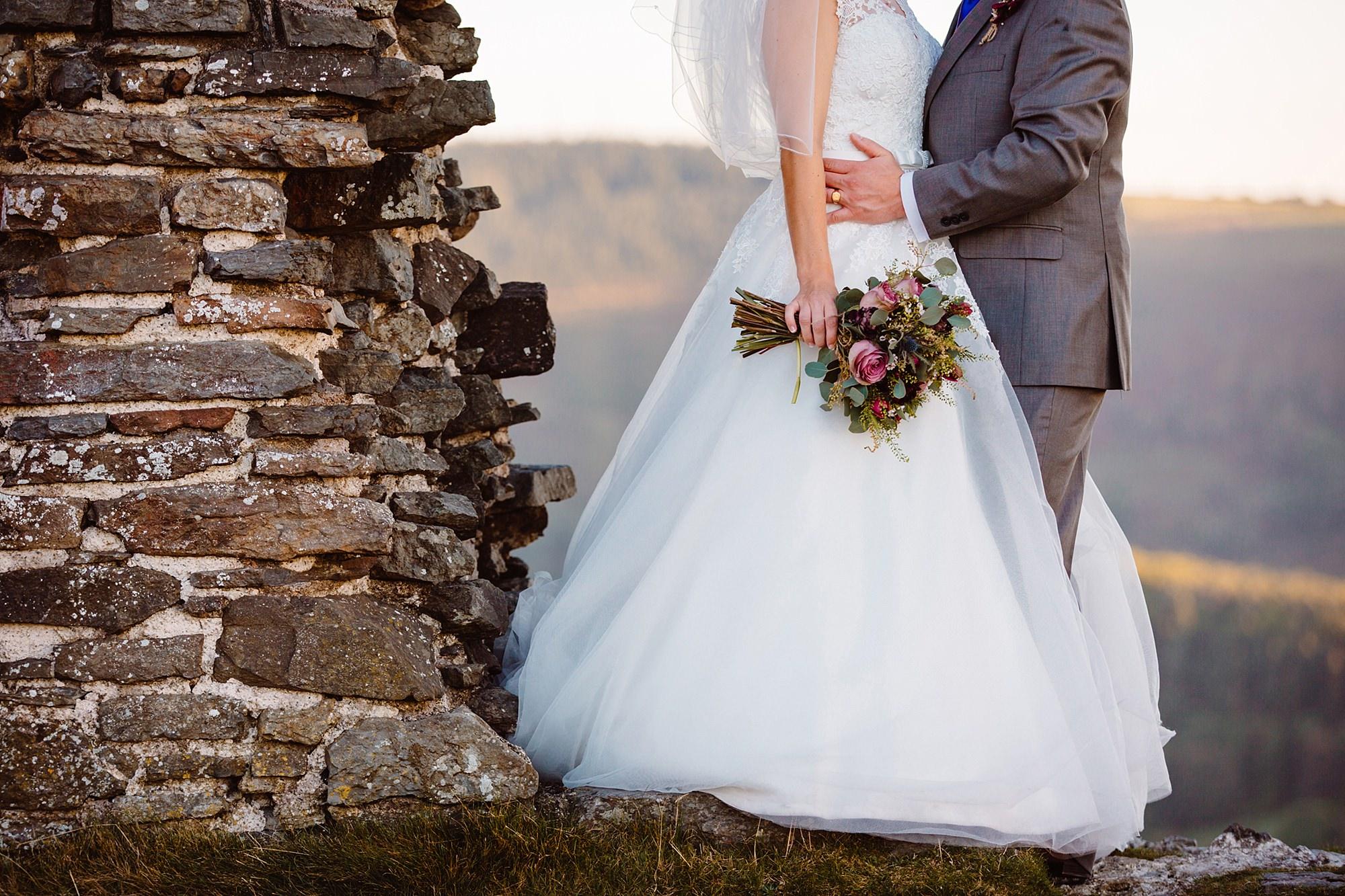 Castell dinas bran wedding photography a closeup detail of bride holding her bouquet at castell dinas bran ruins