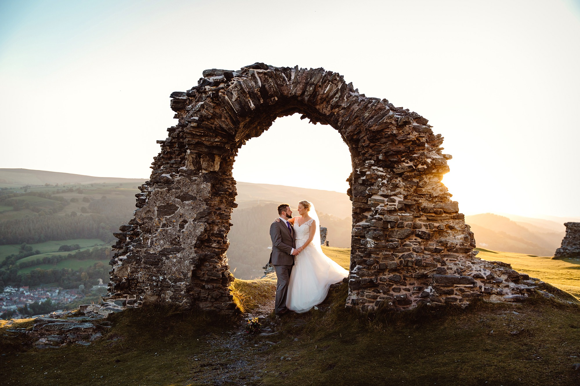 Castell dinas bran wedding photography bride and groom stand under ruined castle arches