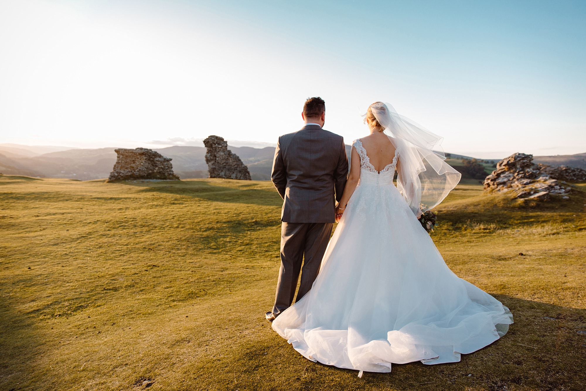 Castell dinas bran wedding photography a bride and groom walk together at castle ruins at sunset