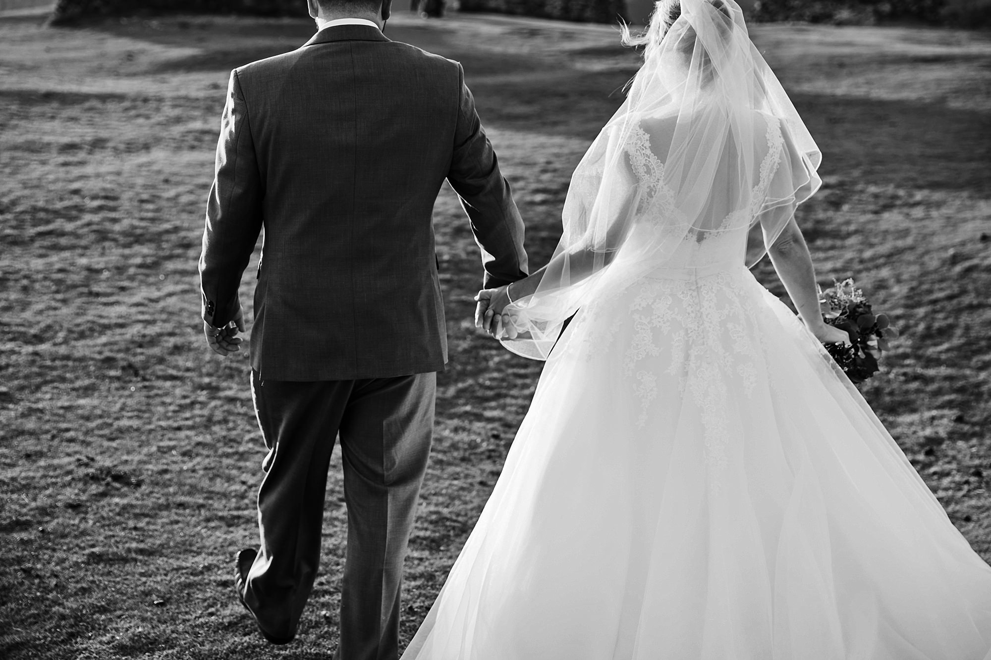 Castell dinas bran wedding photography a bride and groom hold hands as they walk together