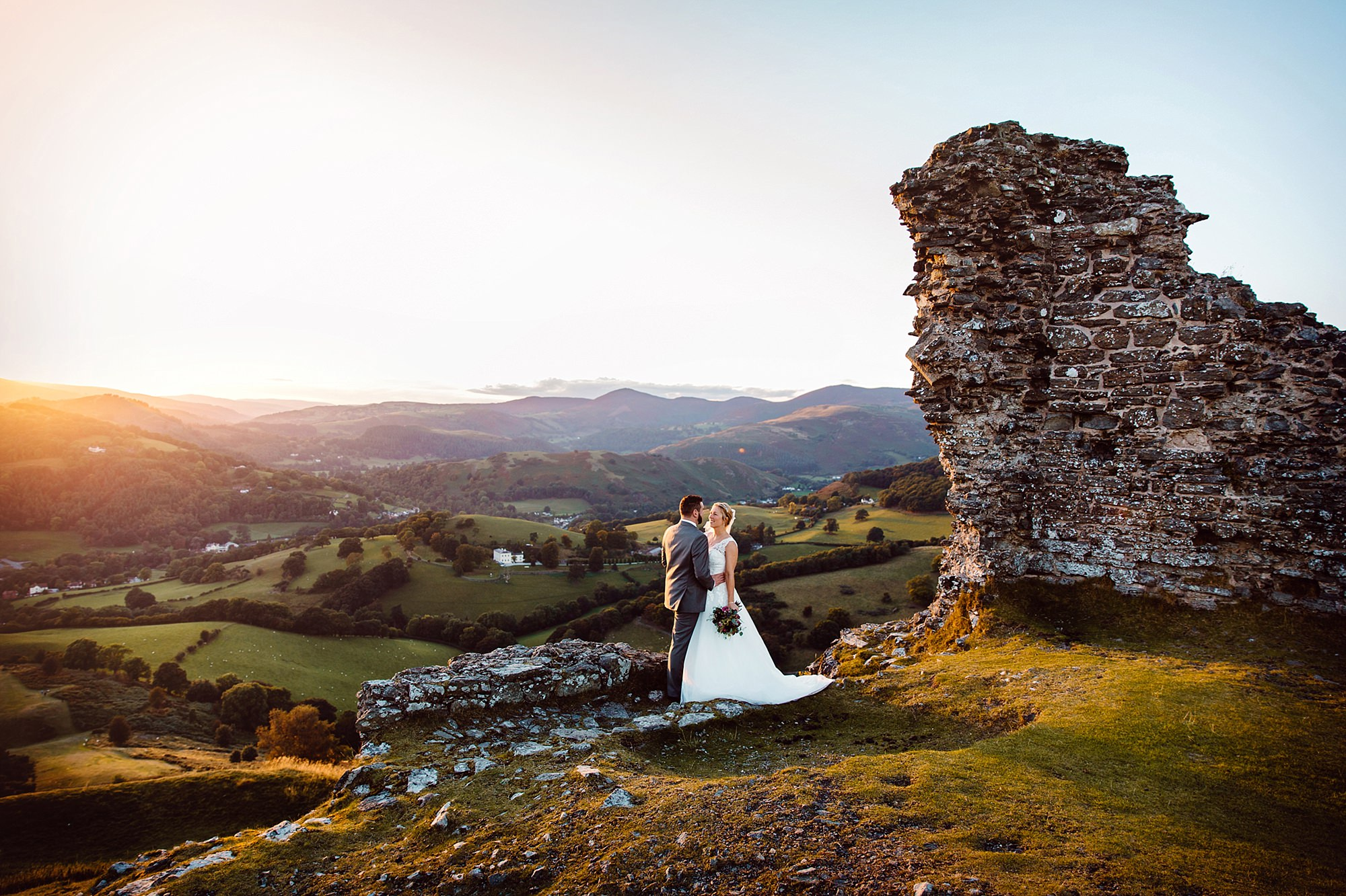 Castell dinas bran wedding photography a bride and groom stand together at castle ruins at sunset