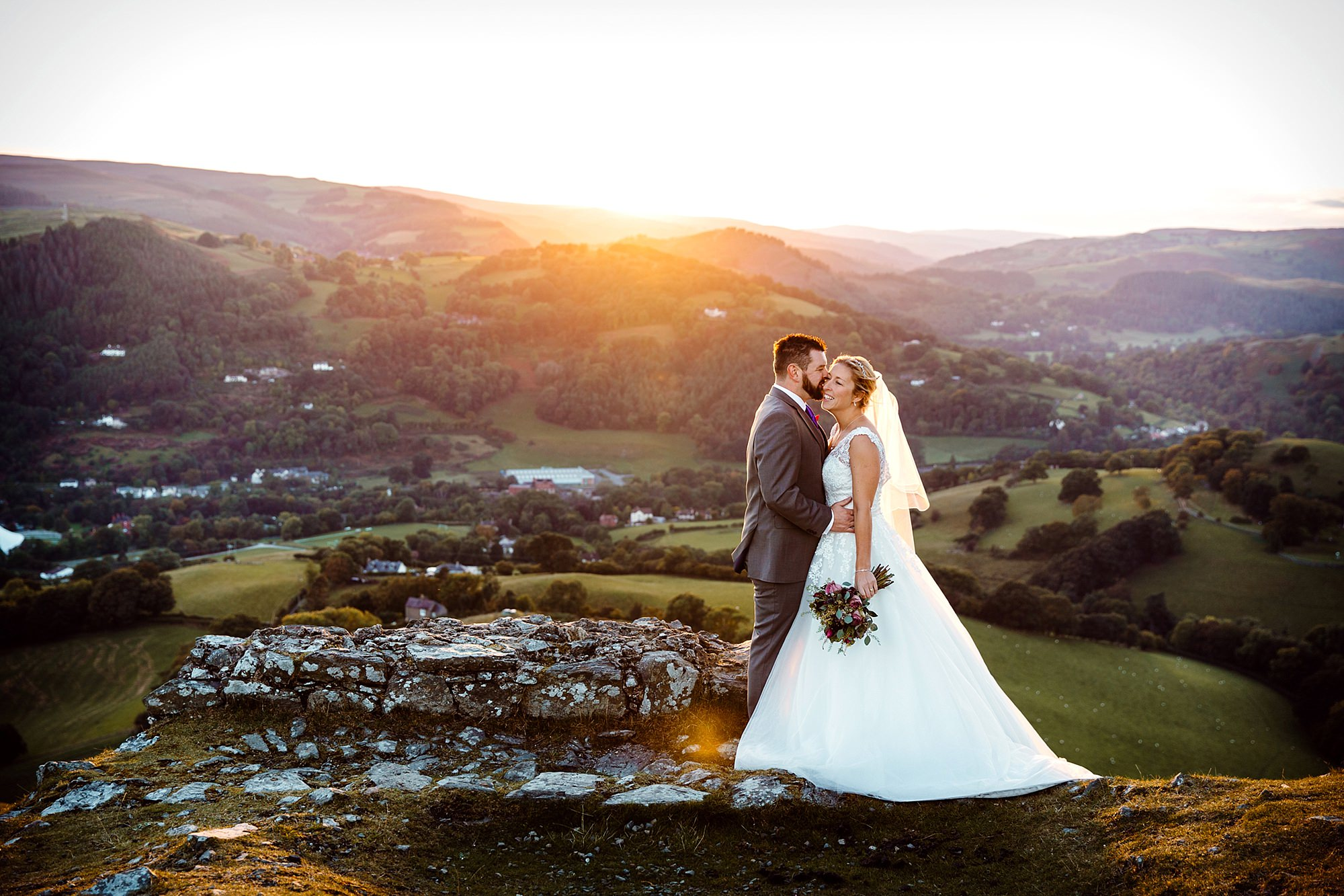 Castell dinas bran wedding photography portrait of bride and groom laughing at ruins at sunset
