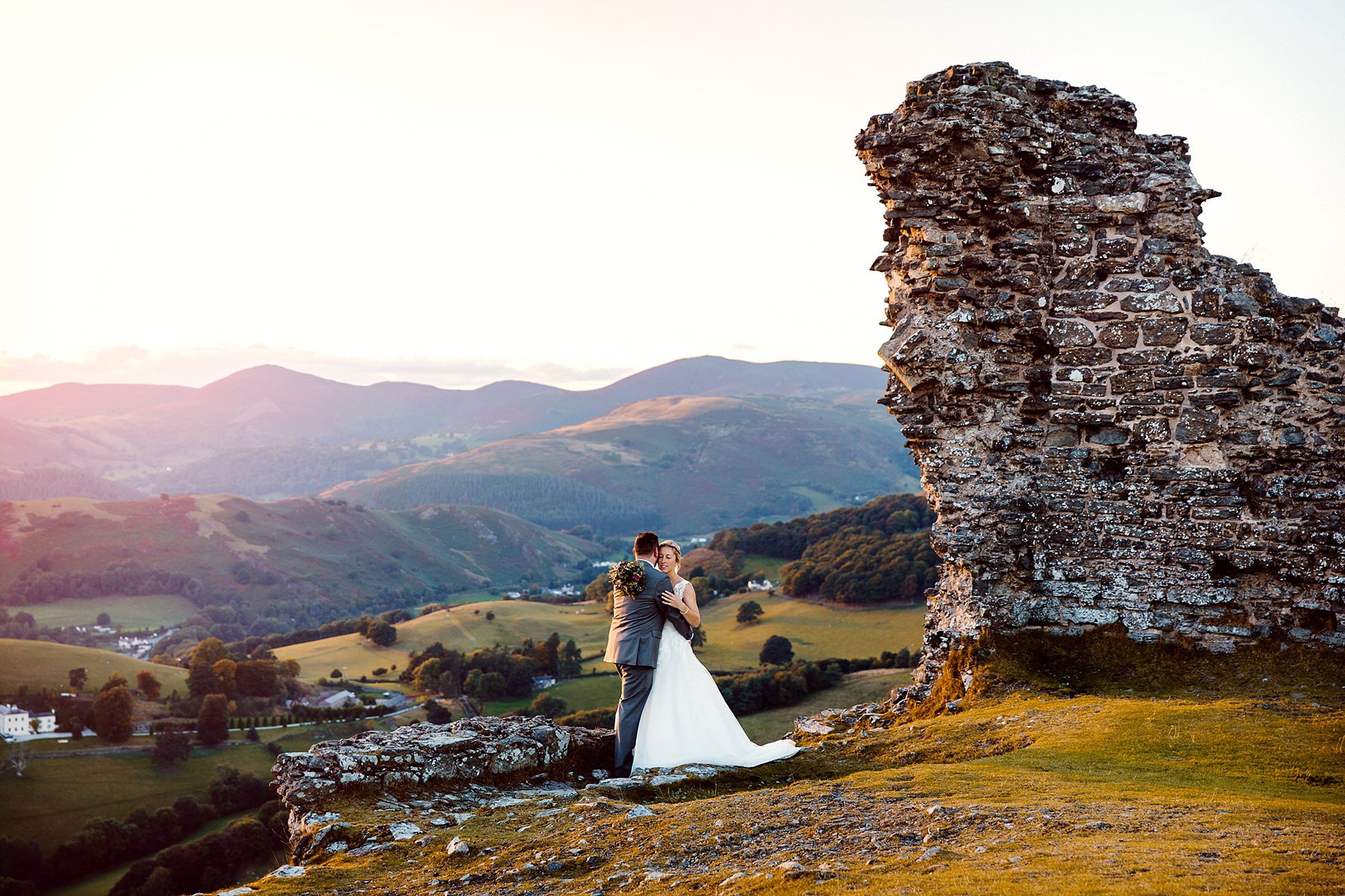 Castell dinas bran wedding photography a bride and groom embrace each other at castle ruins