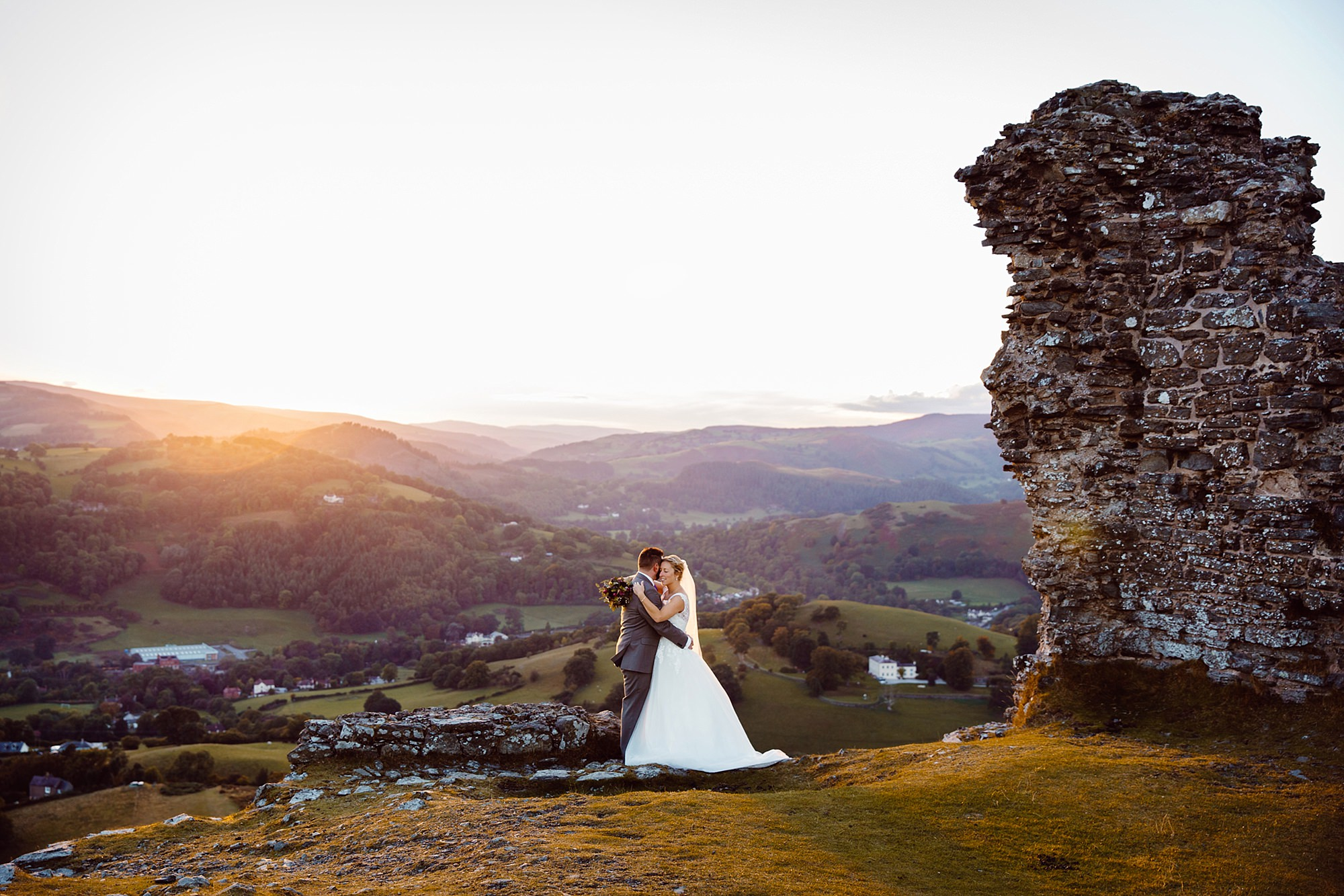 Castell dinas bran wedding photography portrait of bride and groom together at castle ruins at sunset