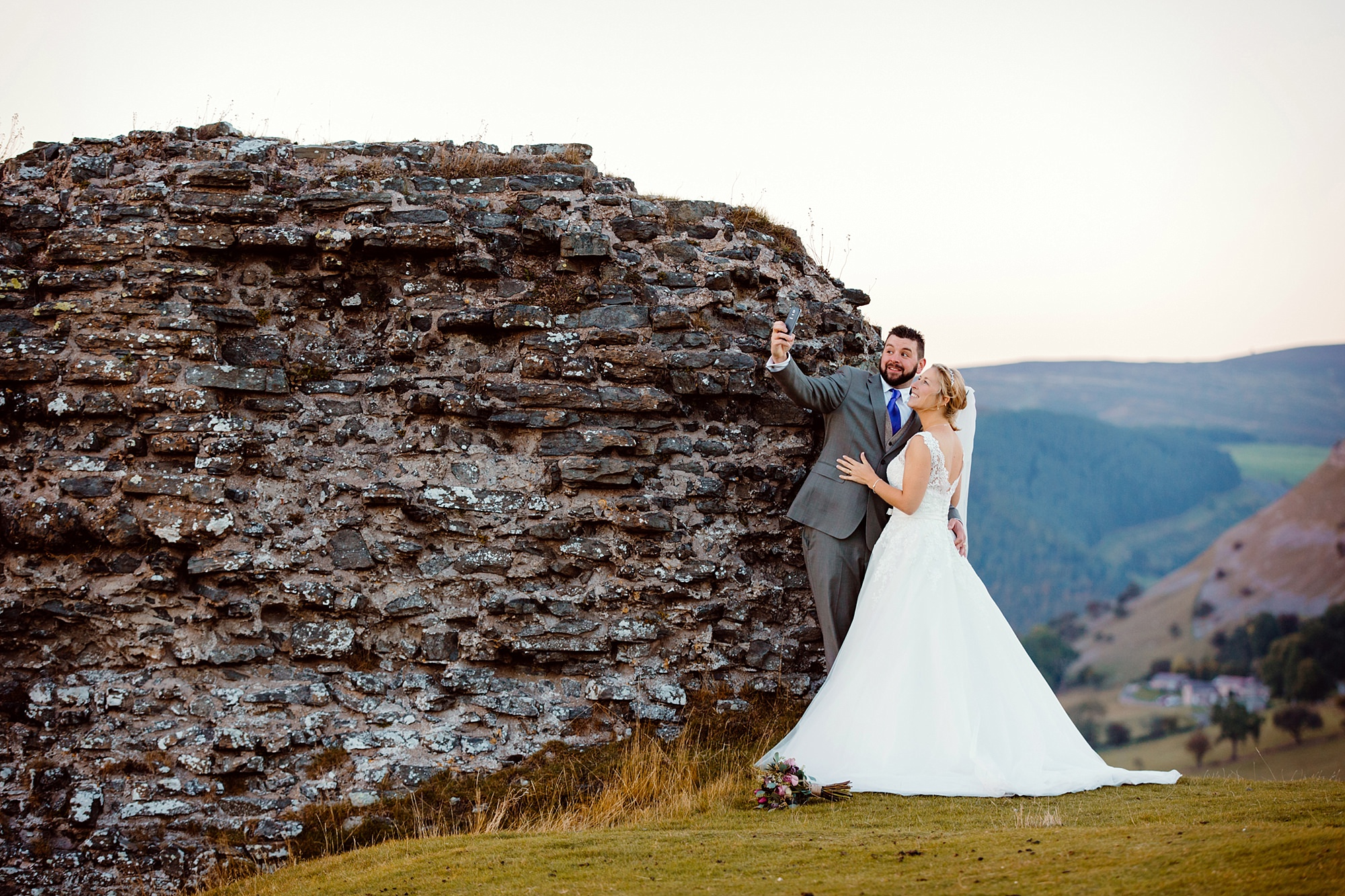 Castell dinas bran wedding photography portrait of bride and groom taking a selfie at castle ruins